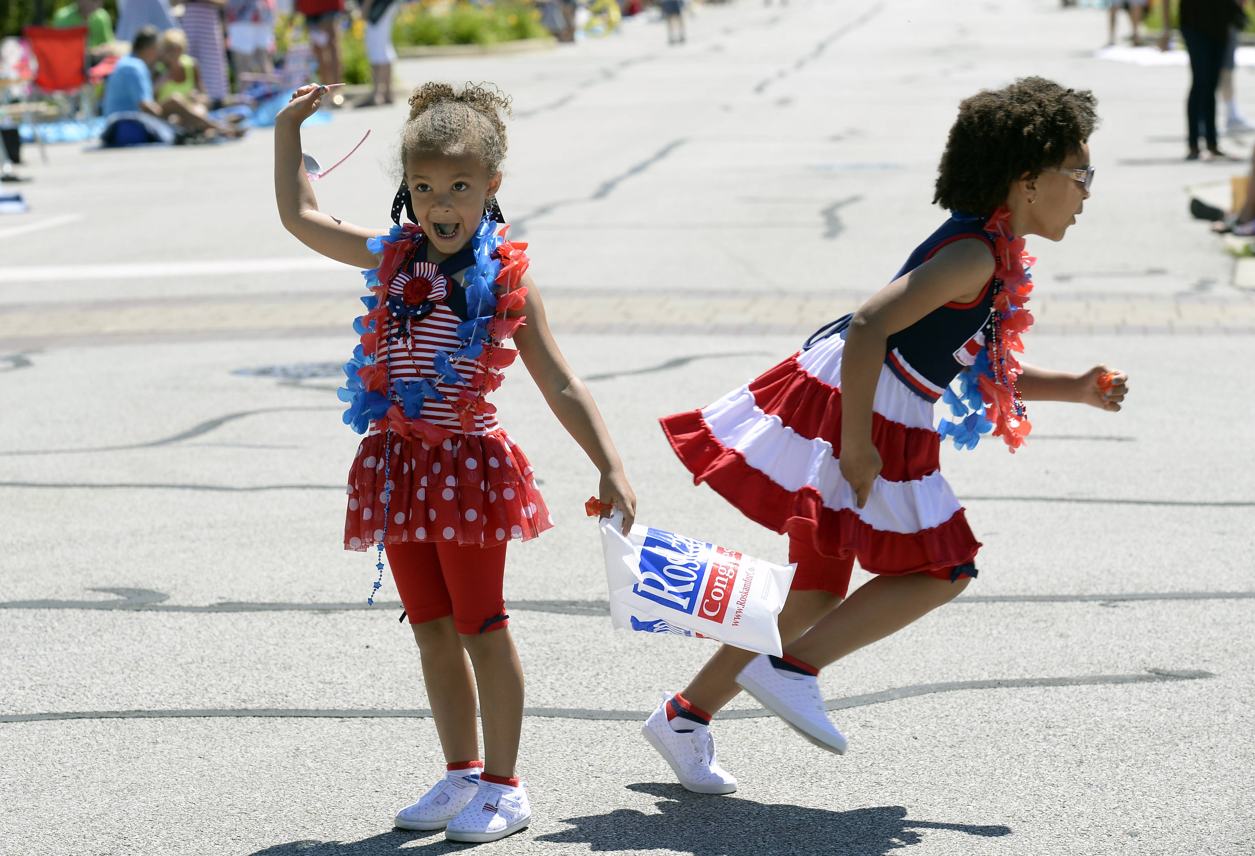 Brianna Akinfala, 4, of Vernon Hills, screams with excitement as the fire trucks come down the street as her sister Sarah, 5, runs for cover at Palatine's annual Hometown Fest Fourth of July parade.