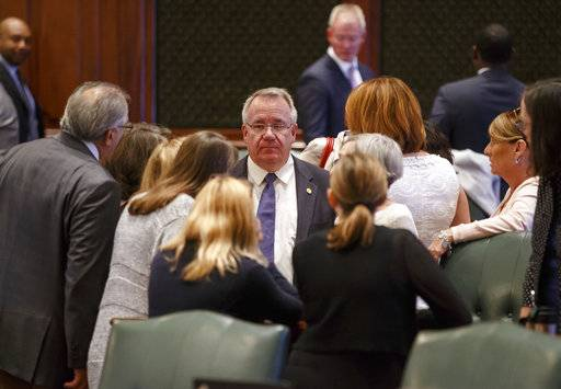 Illinois State Rep. Steve Andersson, R-Geneva, has a discussion on the Democrats side of the aisle on the floor of the Illinois House during the overtime session at the Illinois State Capitol, Saturday, July 1, 2017, in Springfield, Ill. (Justin L. Fowler/The State Journal-Register via AP)
