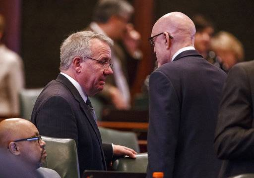 Illinois State Rep. Steve Andersson, R-Geneva, left, talks with Illinois State Rep. Greg Harris, D-Chicago, right, on the floor of the Illinois House during the overtime session at the state Capitol, Sunday, July 2, 2017, in Springfield, Ill. The Illinois House has approved an income tax increase as part of a plan to end the nation's longest budget standoff. (Justin L. Fowler/The State Journal-Register via AP)