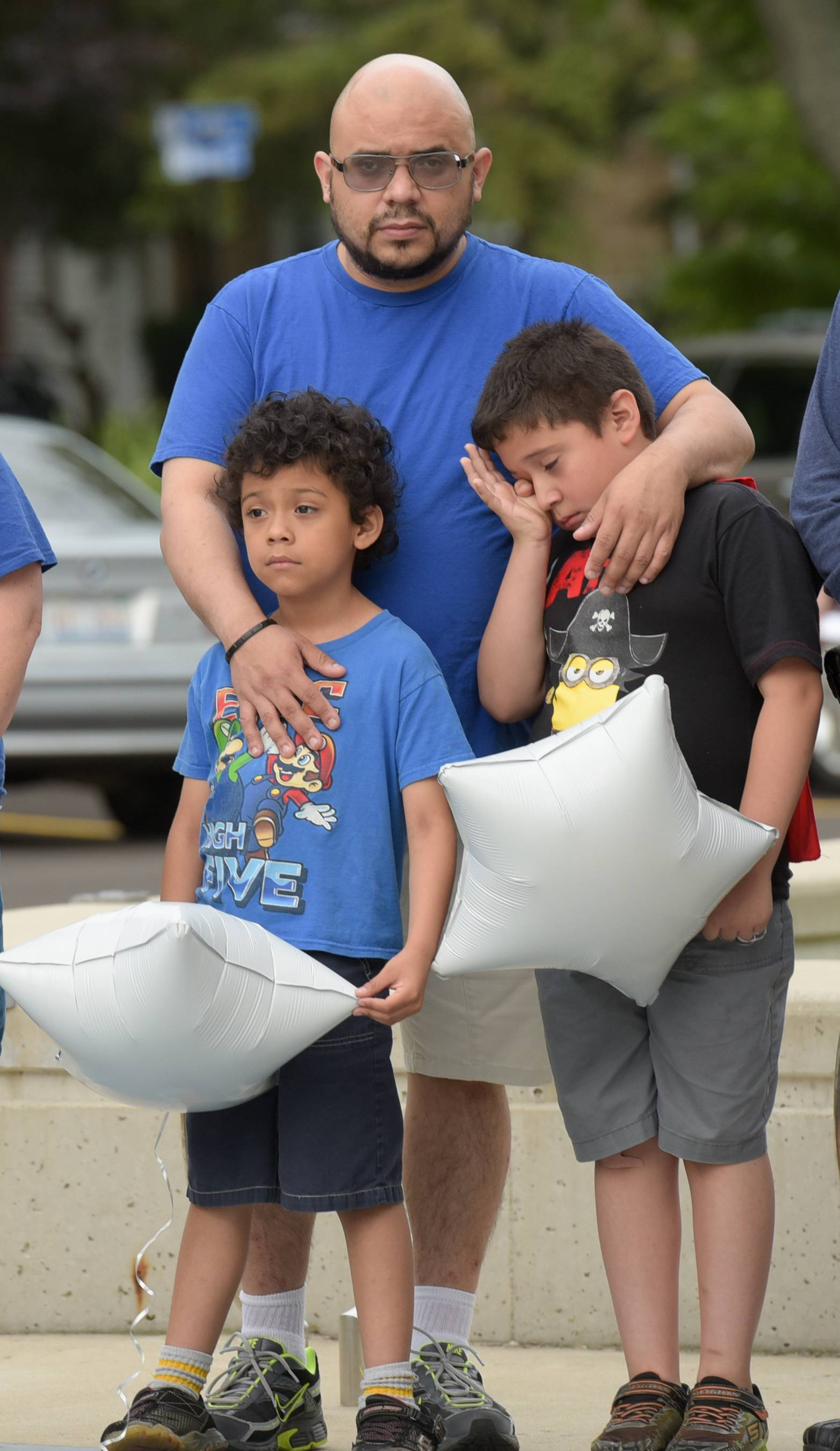 Armando Gomez and his sons, Adrian, 7, and Josue, 9, pay their respects for Thomas DeMauro at Tioga Elementary School in Bensenville on Monday.