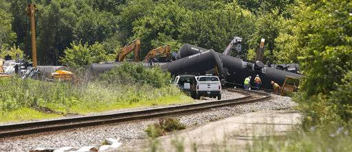 FILE - In this July 1, 2017 file photo, cleanup and containment continues, following the derailment of 20 Canadian National railroad tankers in Plainfield, Ill. Most roads have reopened in Plainfield after the train carrying crude oil derailed about 40 miles southwest of Chicago. Plainfield police say it will take several days to clean up the oil near the village's downtown business district. (Daniel White/Daily Herald via AP, File)