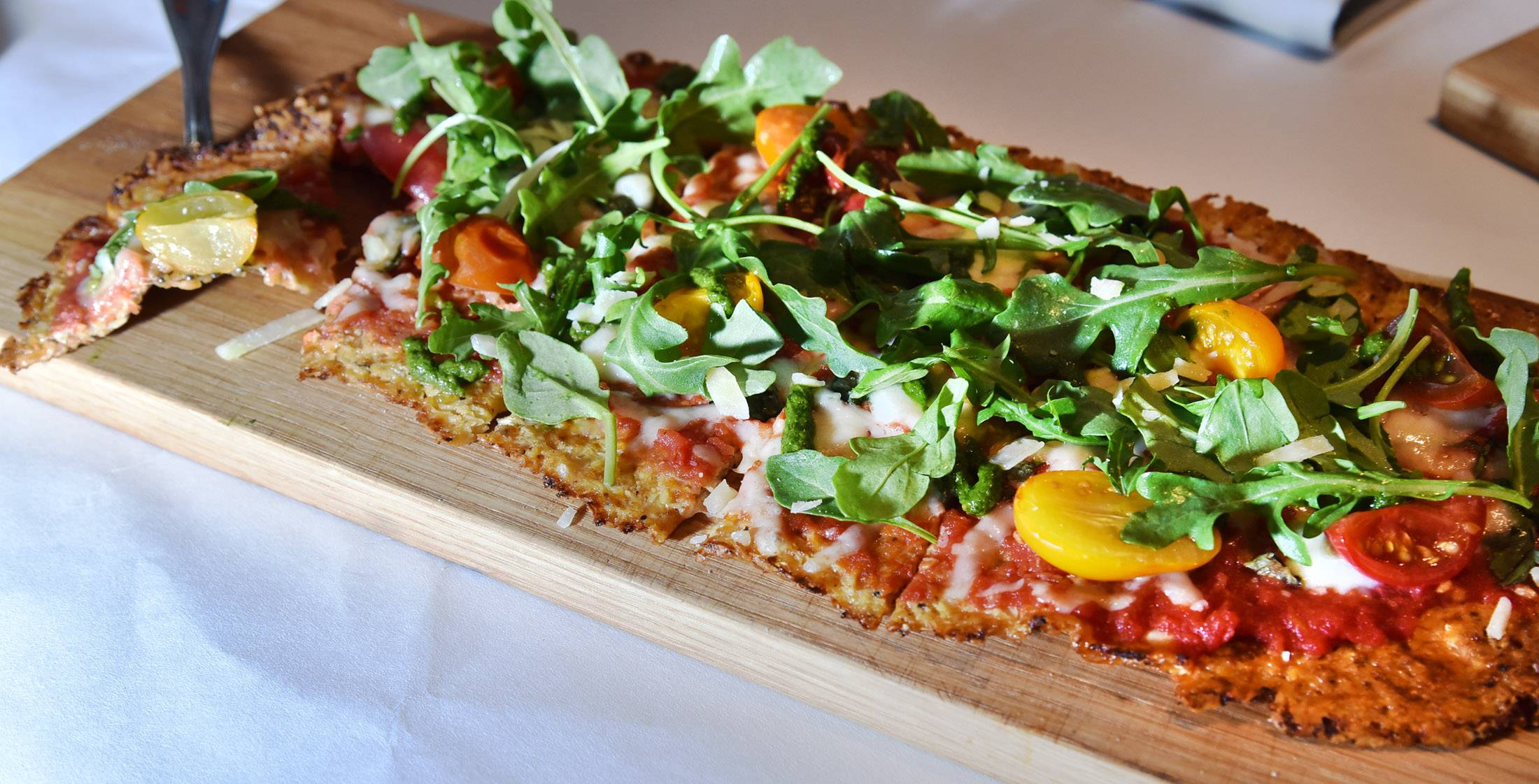 Heirloom cherry tomatoes, mozzarella, pesto and basil top a cauliflower crust for a veggie-lovers version of Livia Italian Eatery's Farmer's Flatbread.