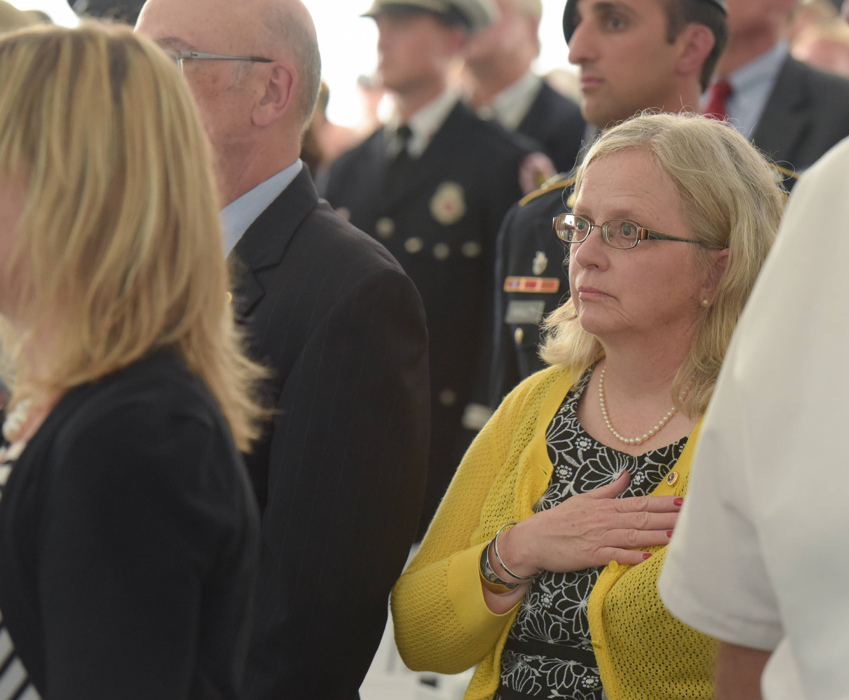 Maureen Miller stands for the national anthem at a ceremony Thursday to name the College of DuPage's Homeland Security Education Center on the Glen Ellyn campus after her son, U.S. Army Staff Sgt. Robert Miller, a Wheaton native who was killed in Afghanistan.