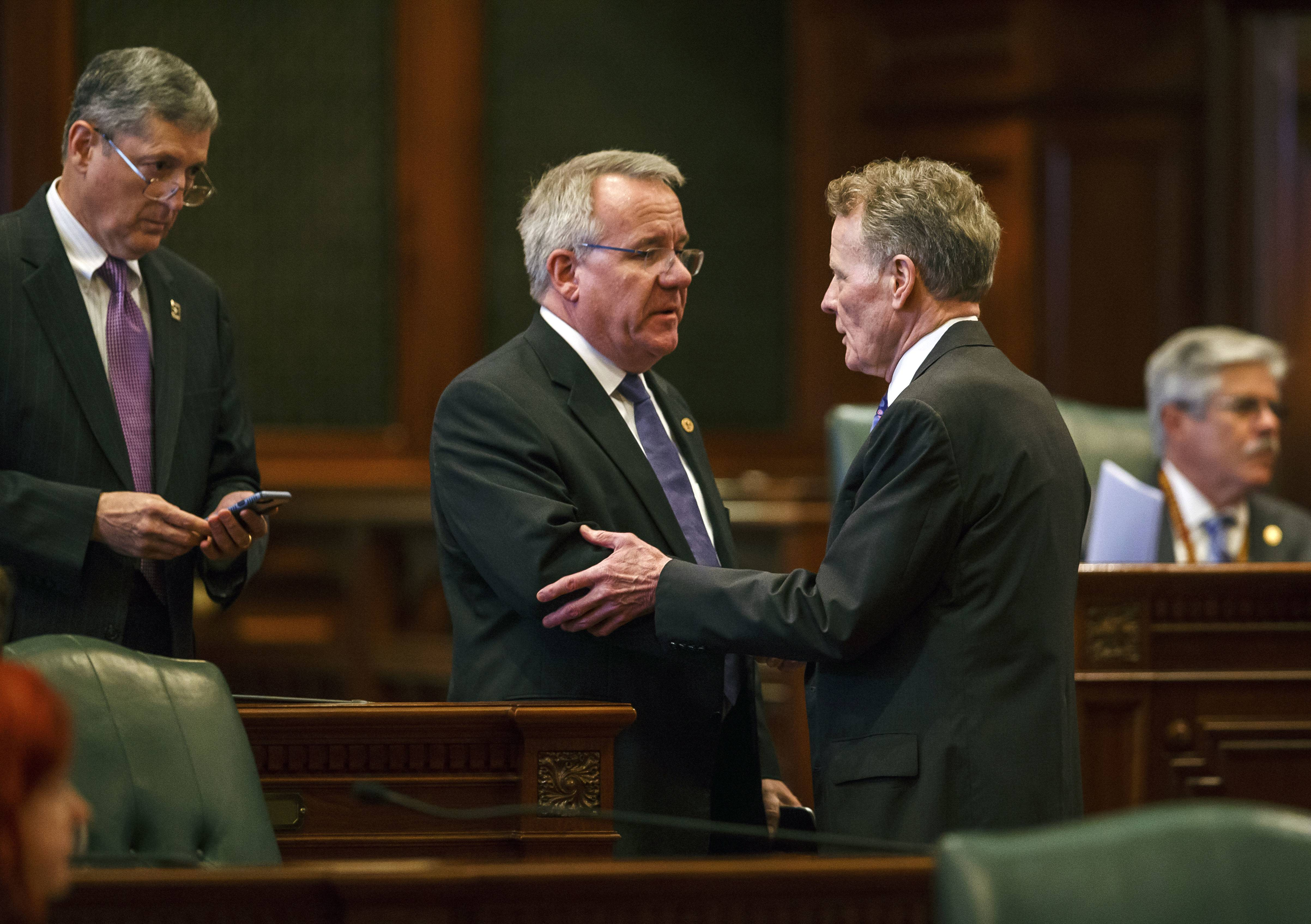 Illinois State Rep. Steve Andersson, R-Geneva, center, shakes hands with Illinois Speaker of the House Michael Madigan, D-Chicago, right, after the Illinois House voted to override Gov. Rauner's veto and pass a budget for the first time in two years during an overtime session at the Illinois State Capitol.