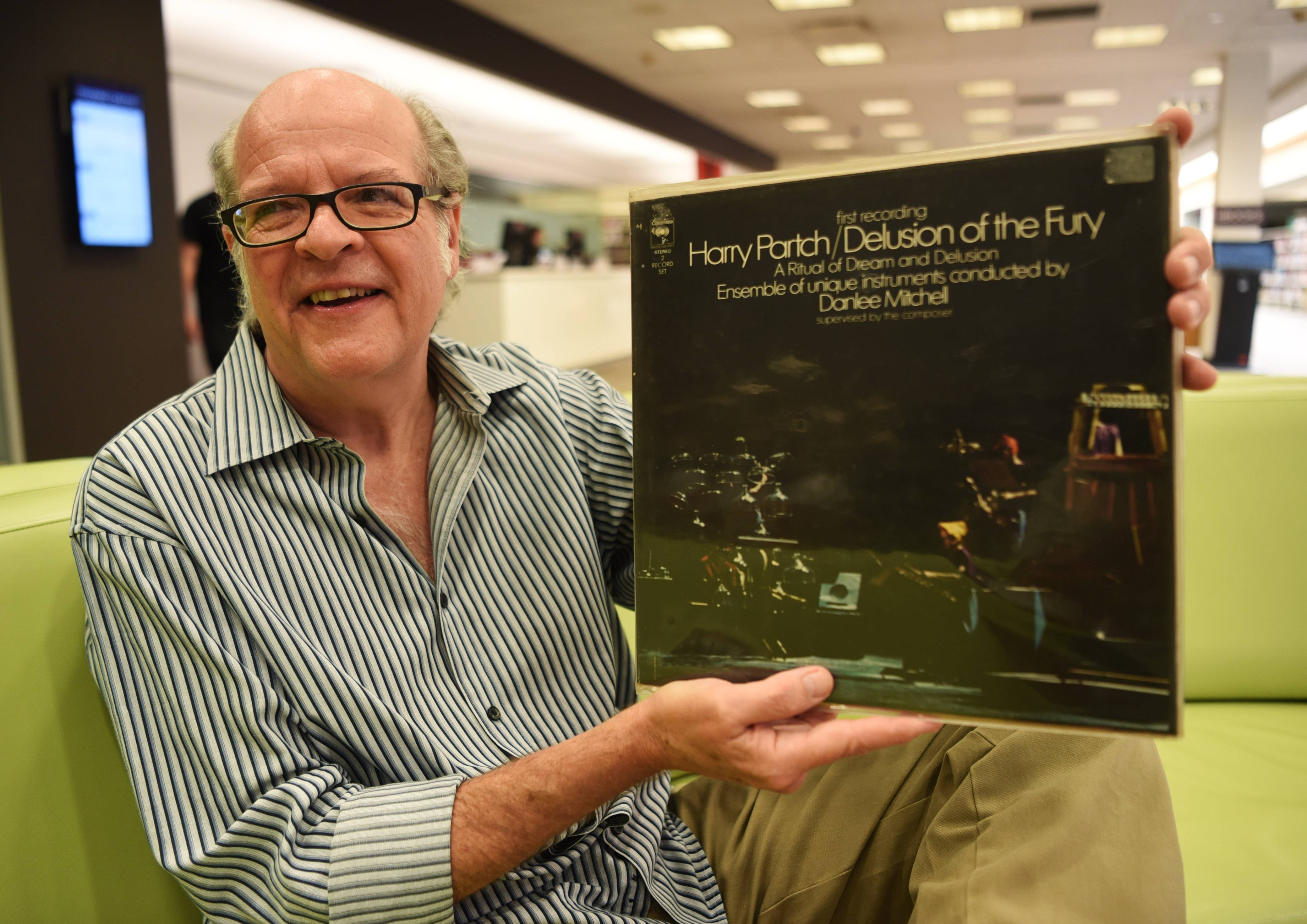 "Bill Paige returns a 1970s vinyl record, ""Delusion of the Fury"" by Harry Partch, to the Arlington Heights Memorial Library Thursday. The local native and longtime Oakton Community College employee, who now lives in Texas, has written a book ""Everything I Know I Learned From Rock Stars."""