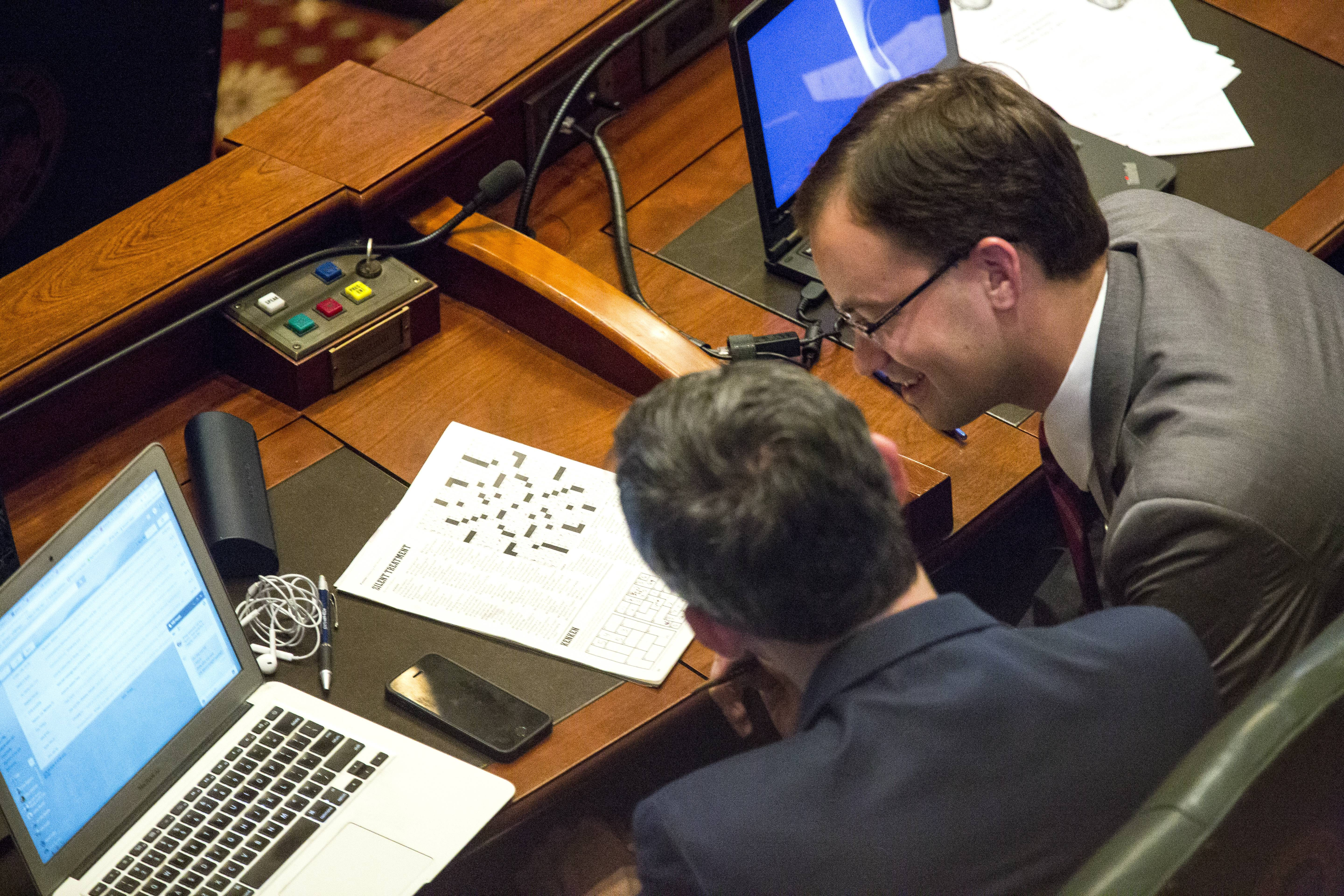 Rep. Will Guzzardi, D-Chicago, left, and Rep. David Olsen, R-Downers Grove, work on a puzzle on the House floor while the state Capitol is on lockdown during a hazardous materials incident Thursday, July 6, 2017 in Springfield, Ill. A financial showdown more than two years in the making was slated to play out in the Illinois House on Thursday as Democrats try to enact a $36 billion spending plan fueled by a 32 percent income tax increase over the Republican governor's objection. (Rich Saal/The State Journal-Register via AP)