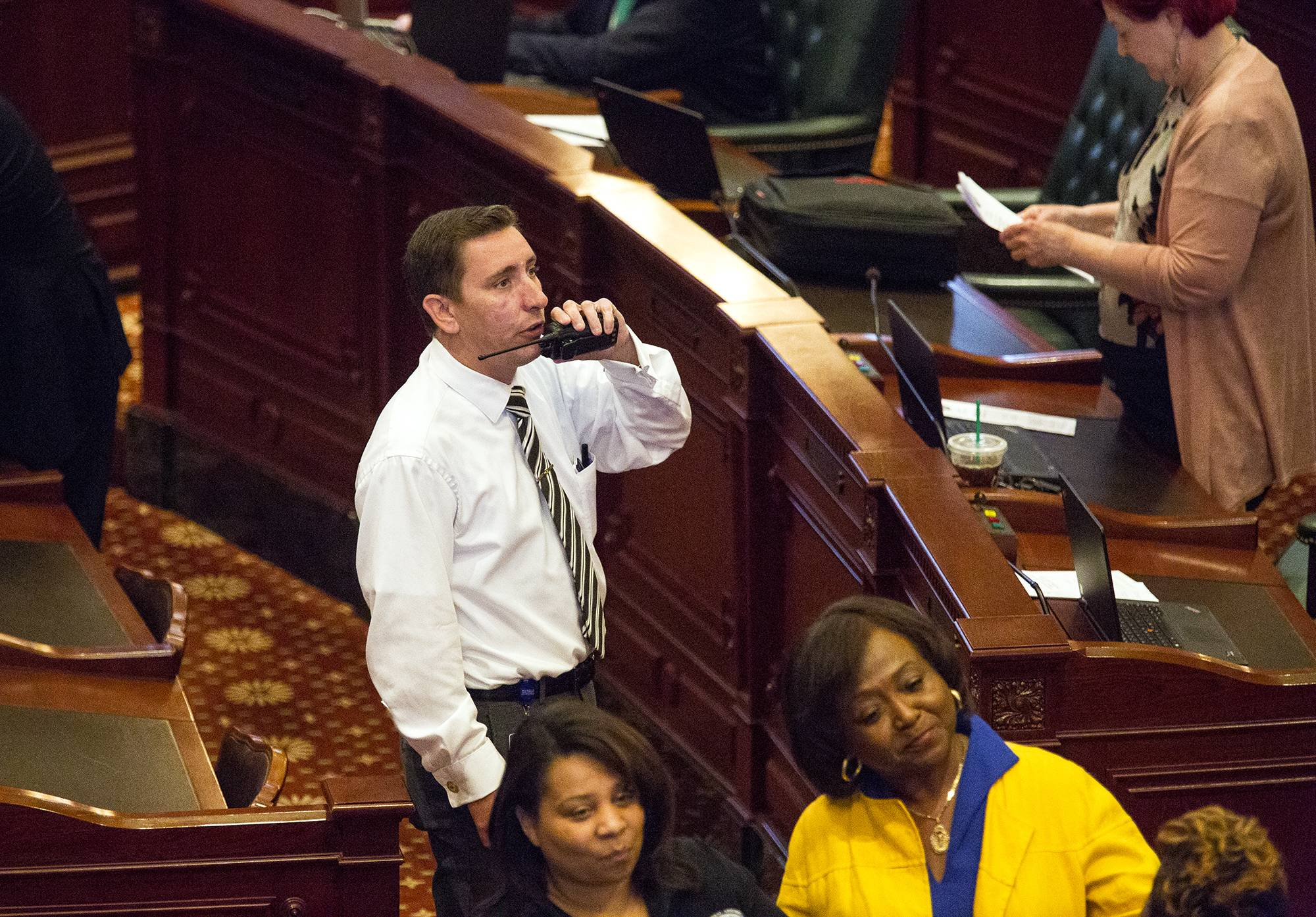 Wayne Padget, House Republican Sergeant at Arms, talks on a radio on the House floor Thursday, July 6, 2017 at the state Capitol in Springfield, Ill. Emergency workers wearing protective gear have entered Gov. Bruce Rauner's office inside the Illinois Capitol after a report of hazardous material that's prompted authorities to block anyone from entering or exiting the building. The investigation has delayed Thursday's critical override vote on a package of bills that could end the state's budget impasse, which has entered a third straight year. (Rich Saal/The State Journal-Register via AP)