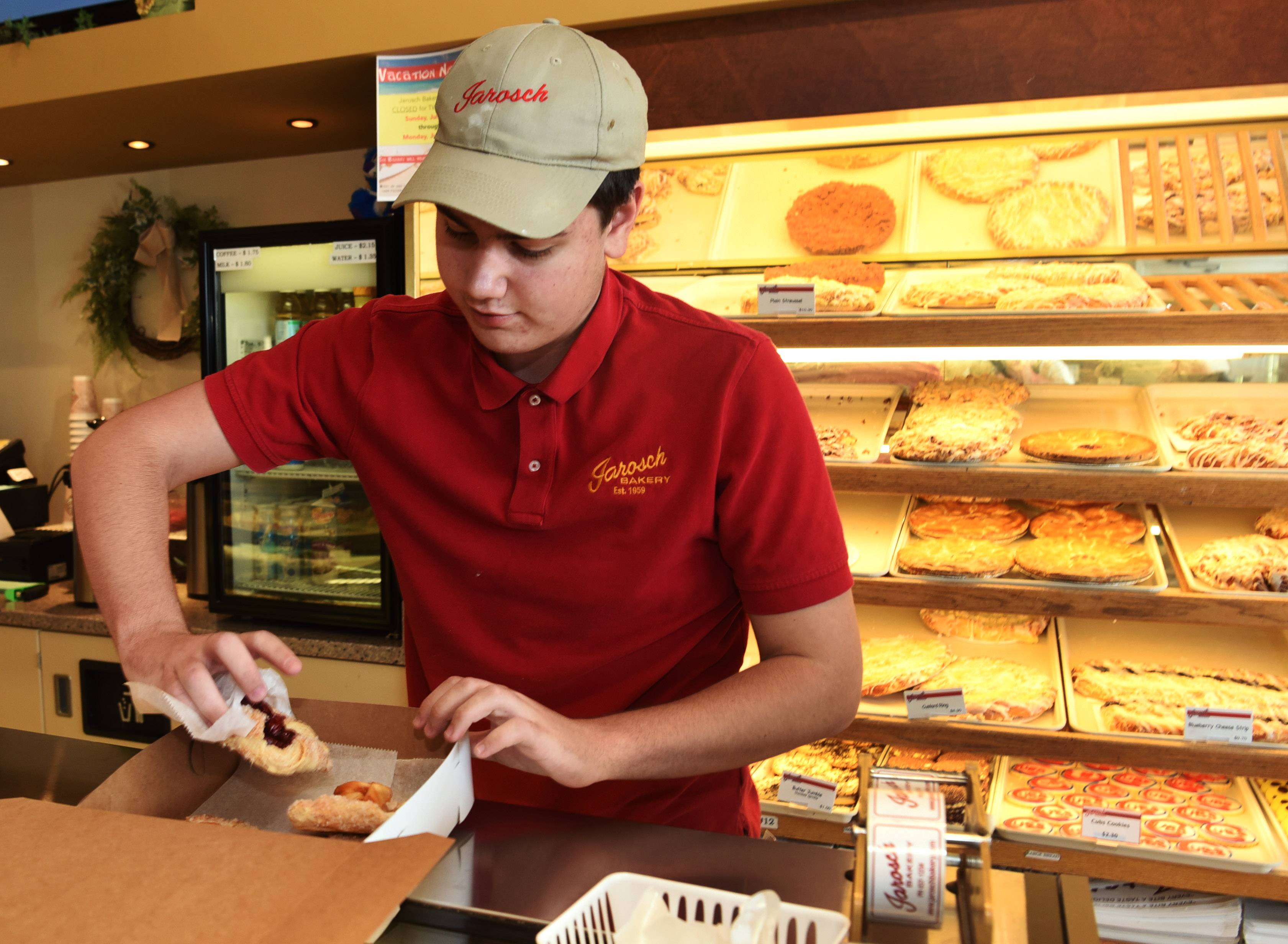 Jack Gallagher, 18, boxes pastries at Jarosch Bakery in Elk Grove Village, one of several Cook County towns to opt out of county ordinances raising the minimum wage and providing sick days.