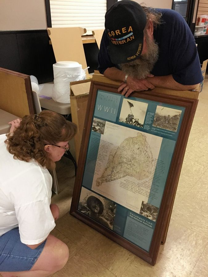 Elgin VFW Post Junior Vice President Shirldine Nohl, left, and Post Commander Art Buckheister check out a map of the Japanese island of Iwo Jima, among old stuff that is being cleared out of the building at 1601 Weld Road.
