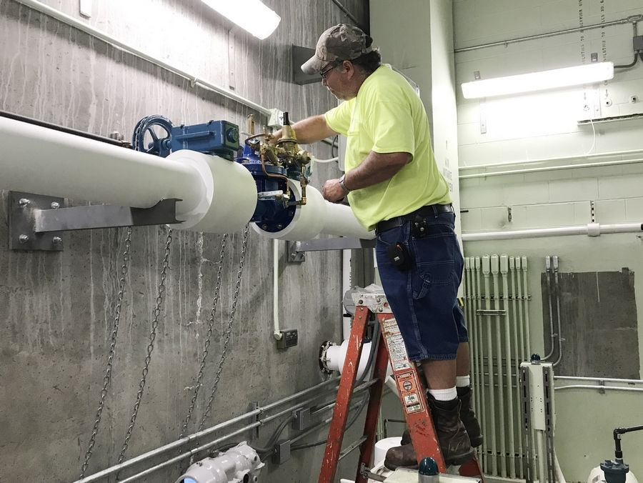 A worker checks equipment associated with bringing Lake Michigan water to Grandwood Park.