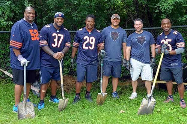 Representatives of the Chicago Bears, from left: Mickey Pruitt, Jason McKie, Adrian Peterson, Jared Ellerson, Adam Kellner and Garrett Wolfe help put in a new fence at A Safe Place's emergency shelter.