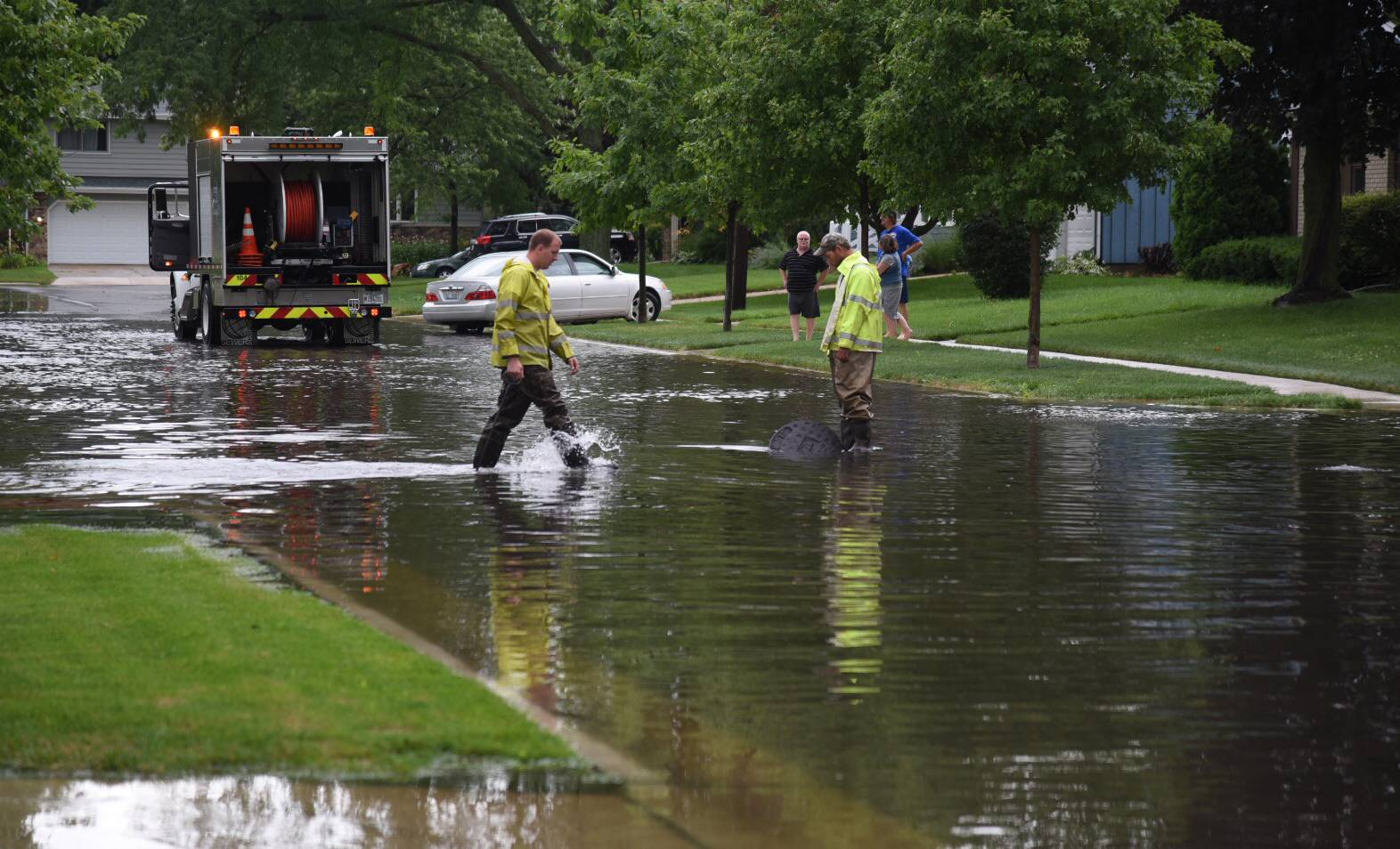City of Elgin public works employees work to clear drains on Jane Drive on Wednesday morning after drenching rains caused flooding in streets and houses.