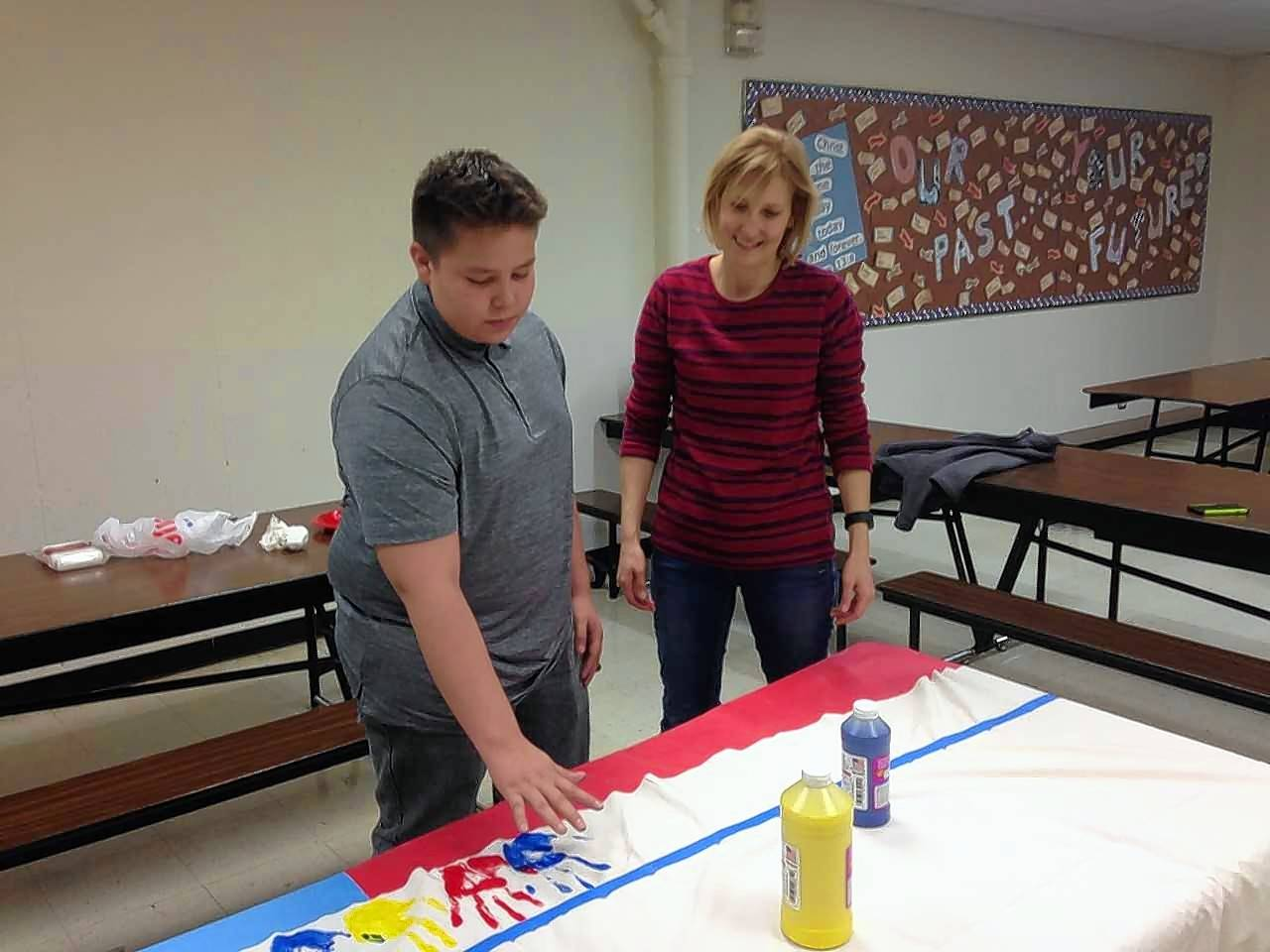 St. John Lutheran School in Elgin celebrated its 150th anniversary this year. Ethan Zimmerman, 13, of Elgin places his handprint on an 150th anniversary banner with the help of parent volunteer Tracy Schatz.