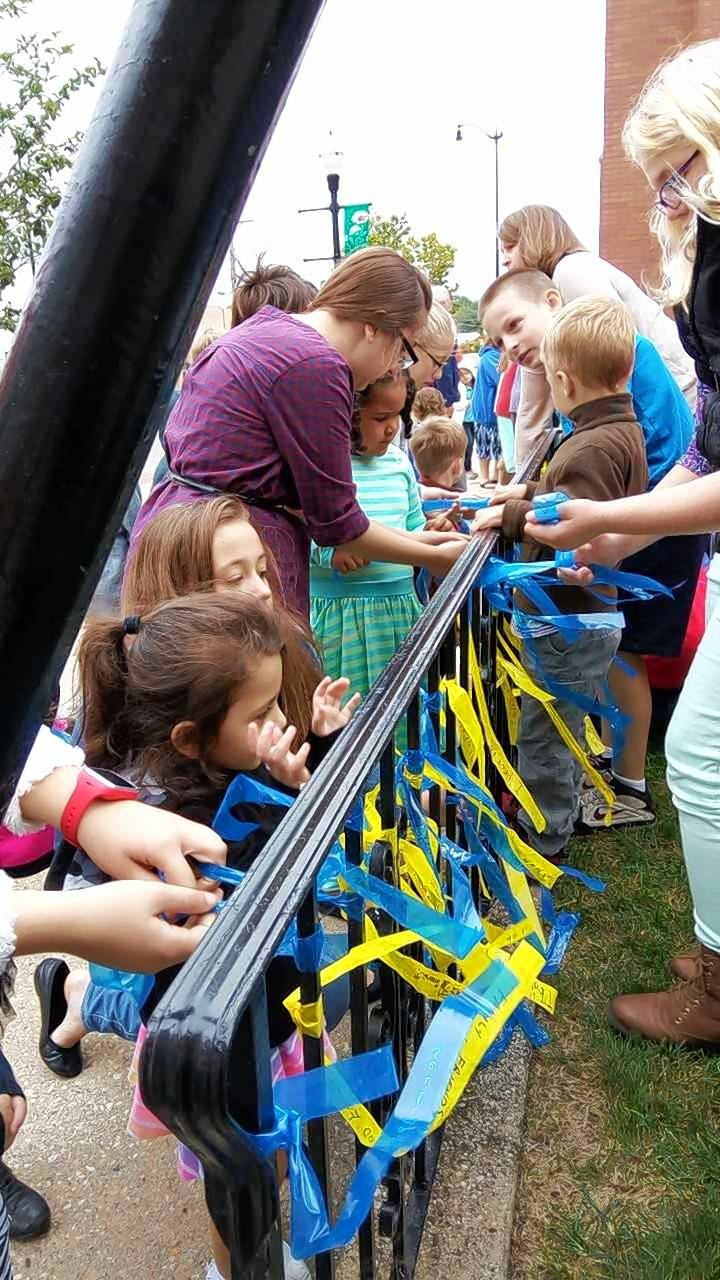 Students put prayer ribbons on a fence to celebrate the 150th school year at St. John's Lutheran School in Elgin.