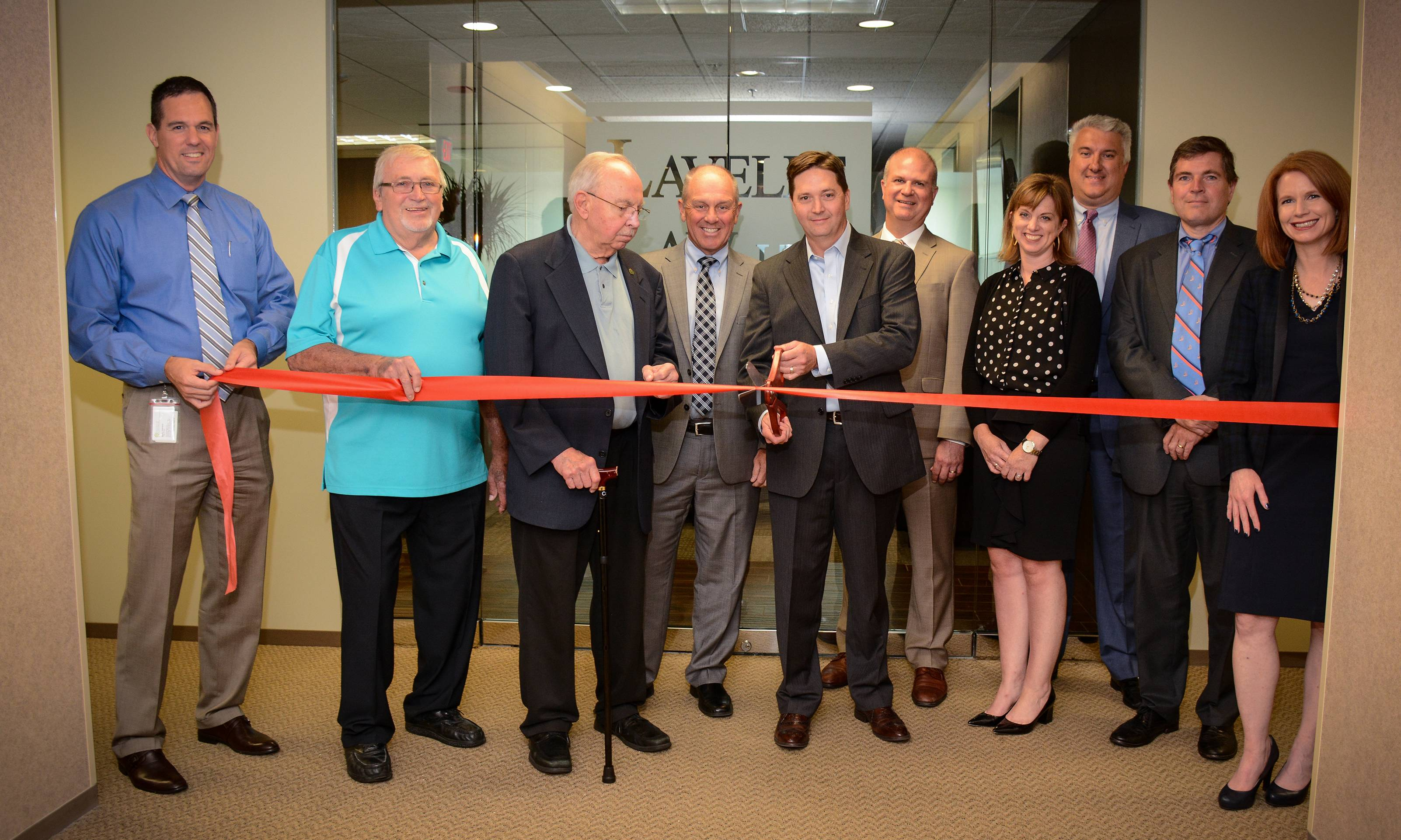 Schaumburg Mayor Al Larson and other village officials join Lavelle Law Managing Partner Ted McGinn and other partners in the firm at a ribbon cutting ceremony.