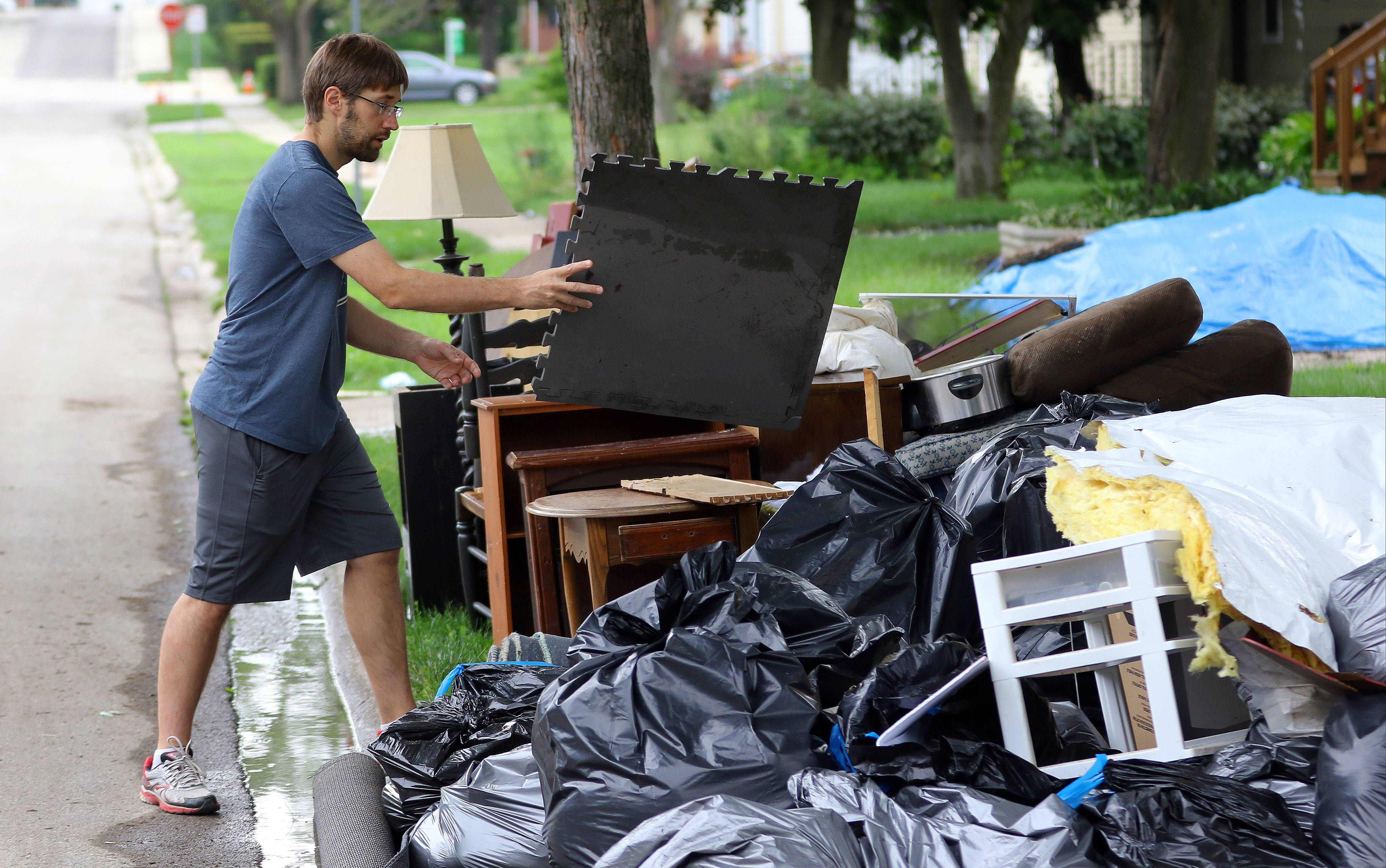 Chris Walter of Mundelein throws out flooded items from his basement as people clean up from Wednesday's flooding.