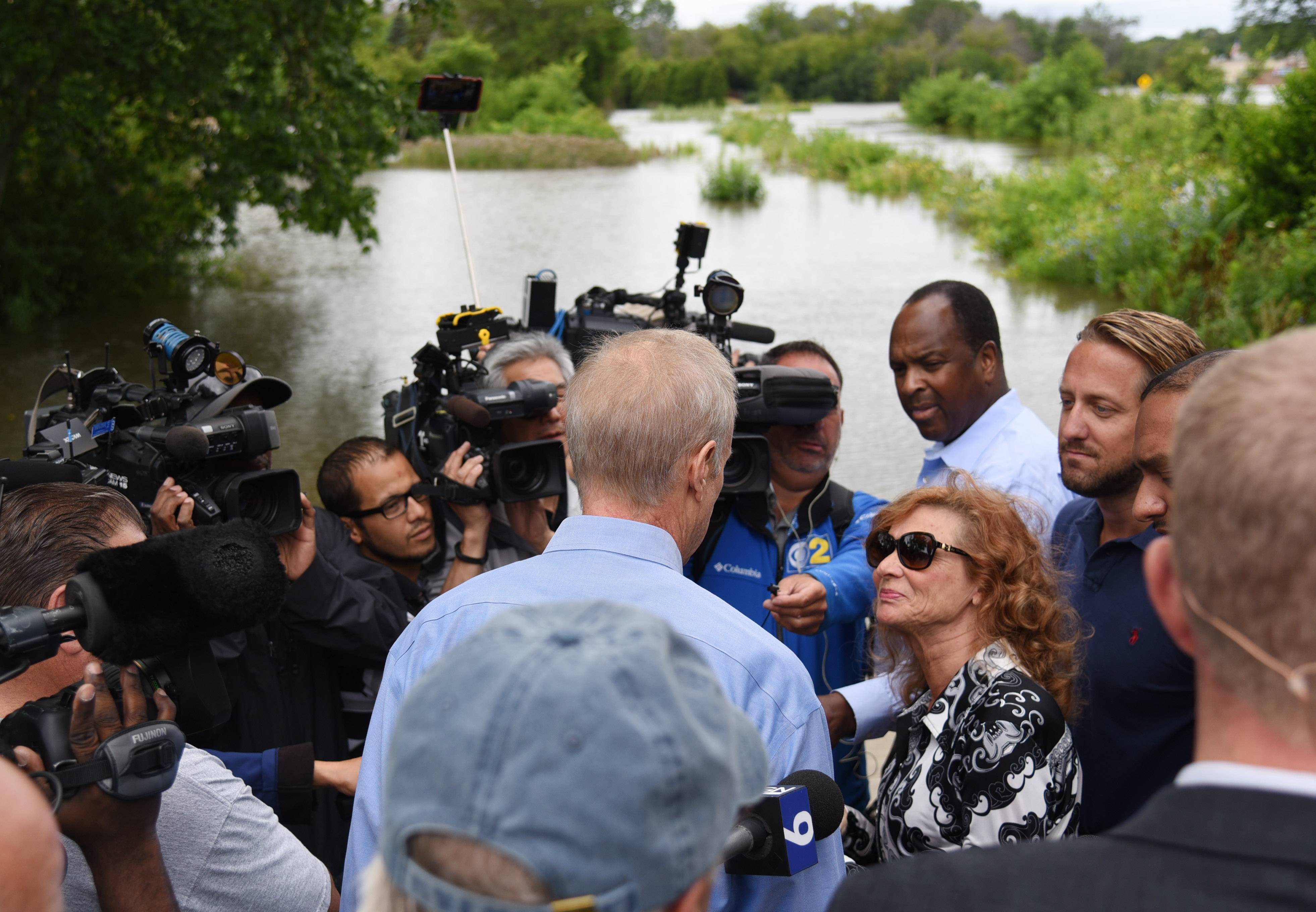 Paul Valade/pvalade@dailyherald.comGurnee Mayor Kristina Kovarik, bottom right, talks with Illinois Gov.  Bruce Rauner as he surveys flooding Friday morning near Grand Avenue and O'Plaine Road in Gurnee. Lake County Board Chairman Aaron Lawlor, right, listens in.