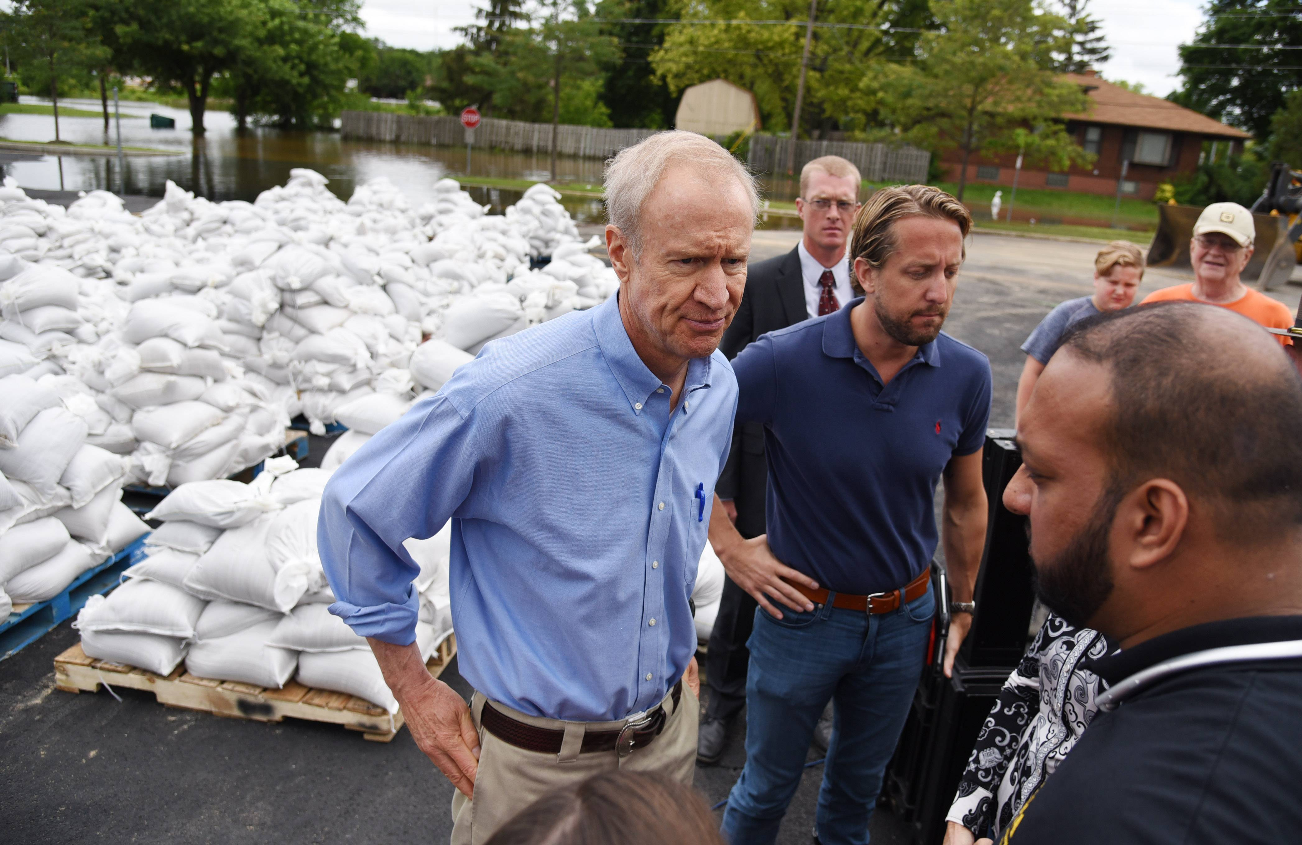 Paul Valade/pvalade@dailyherald.comIllinois Gov. Bruce Rauner, left, pauses near hundreds of sandbags and the flooded McClure Avenue, back left, with Lake County Board Chairman Aaron Lawlor and IEMA Director James Joseph, right, Friday during a stop in Gurnee to survey flood damage.