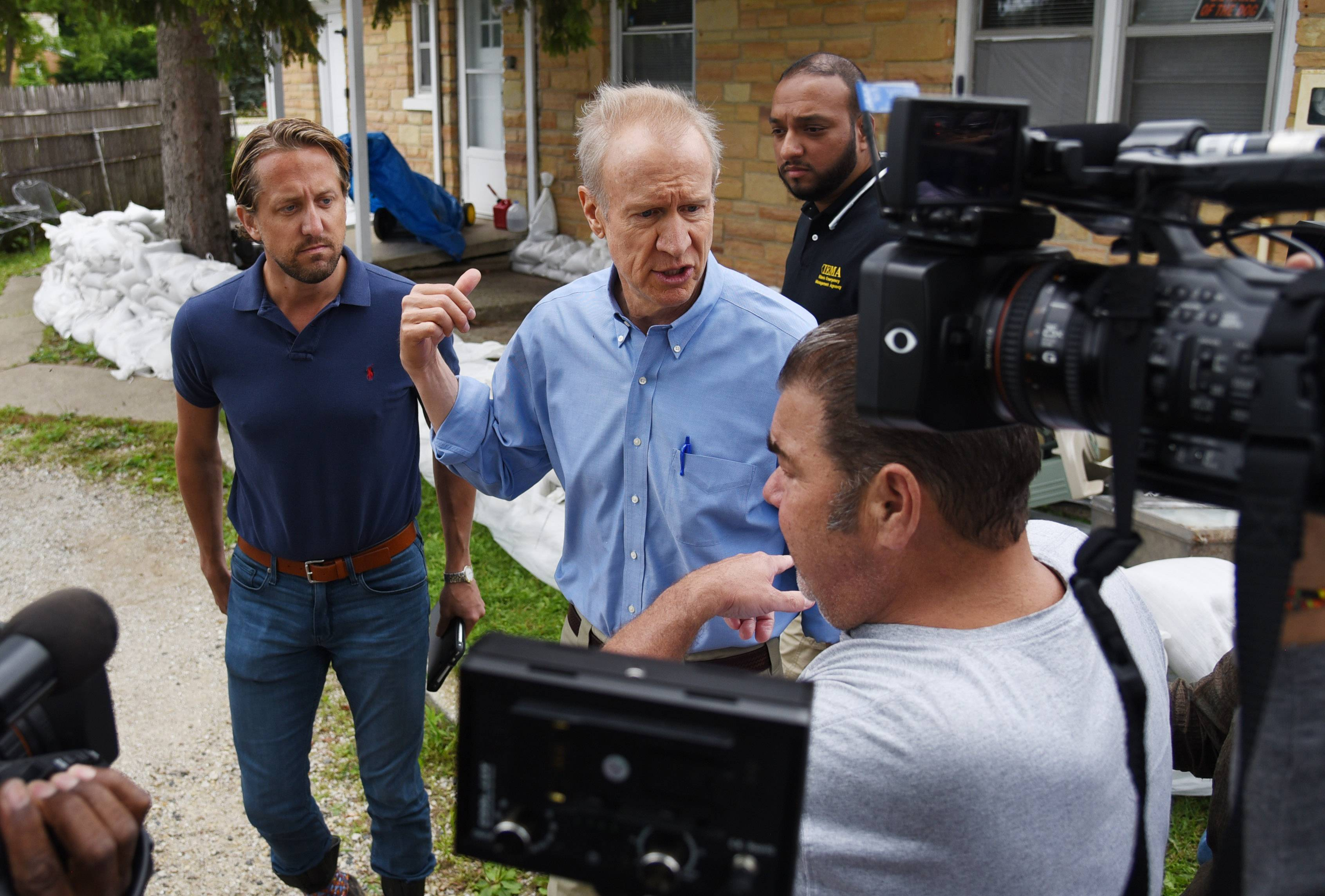 Gov. Bruce Rauner, center, talks with Gurnee homeowner Shawn Depke, right, as they survey the rising Des Plaines River near his houses at Grand Avenue and O'Plaine Road Friday.