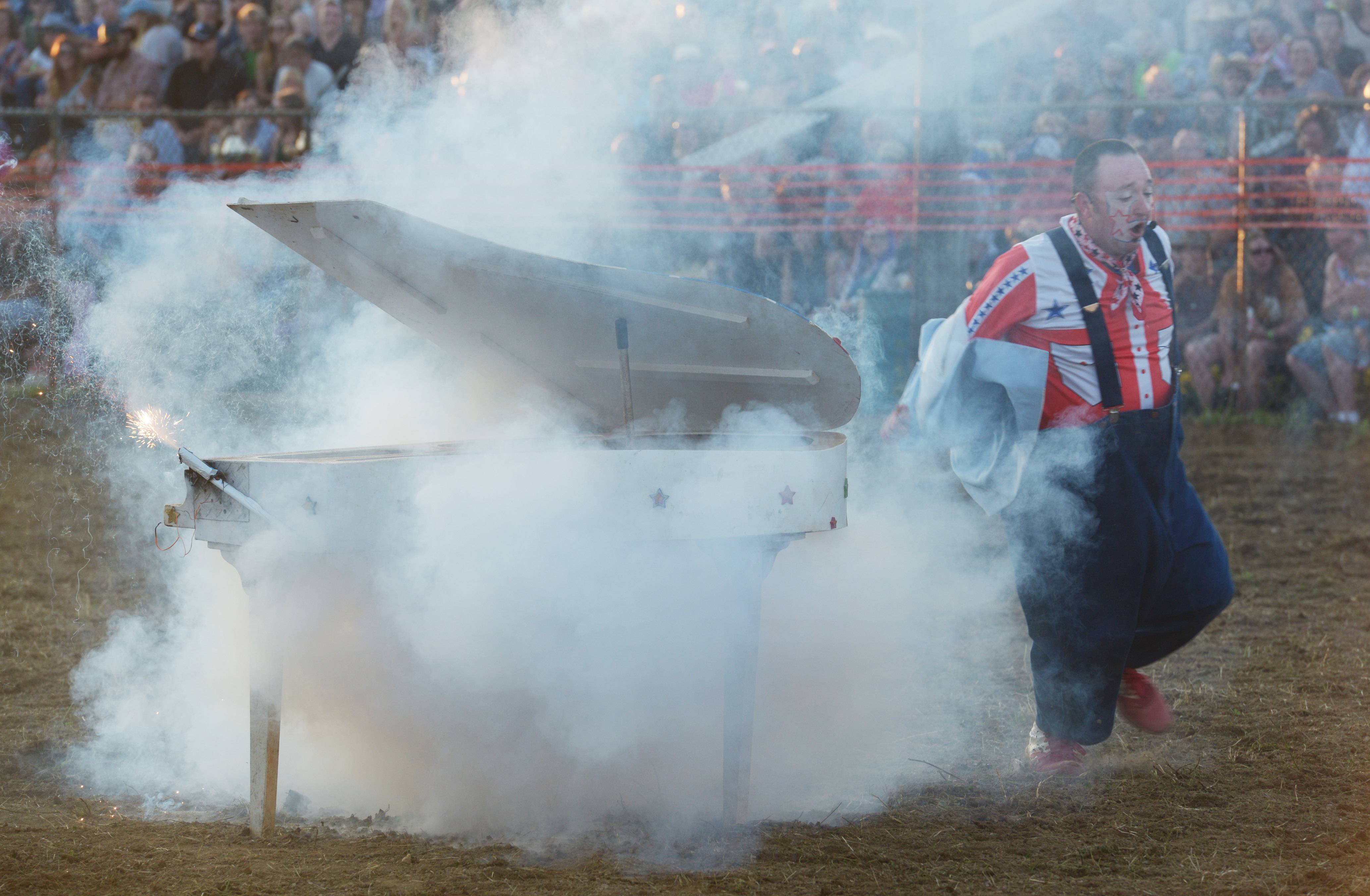"Rodeo clown Eugene Fowler runs away from his exploding piano after playing ""Great Balls of Fire"" during the 54th annual IPRA Championship rodeo Saturday in Wauconda."