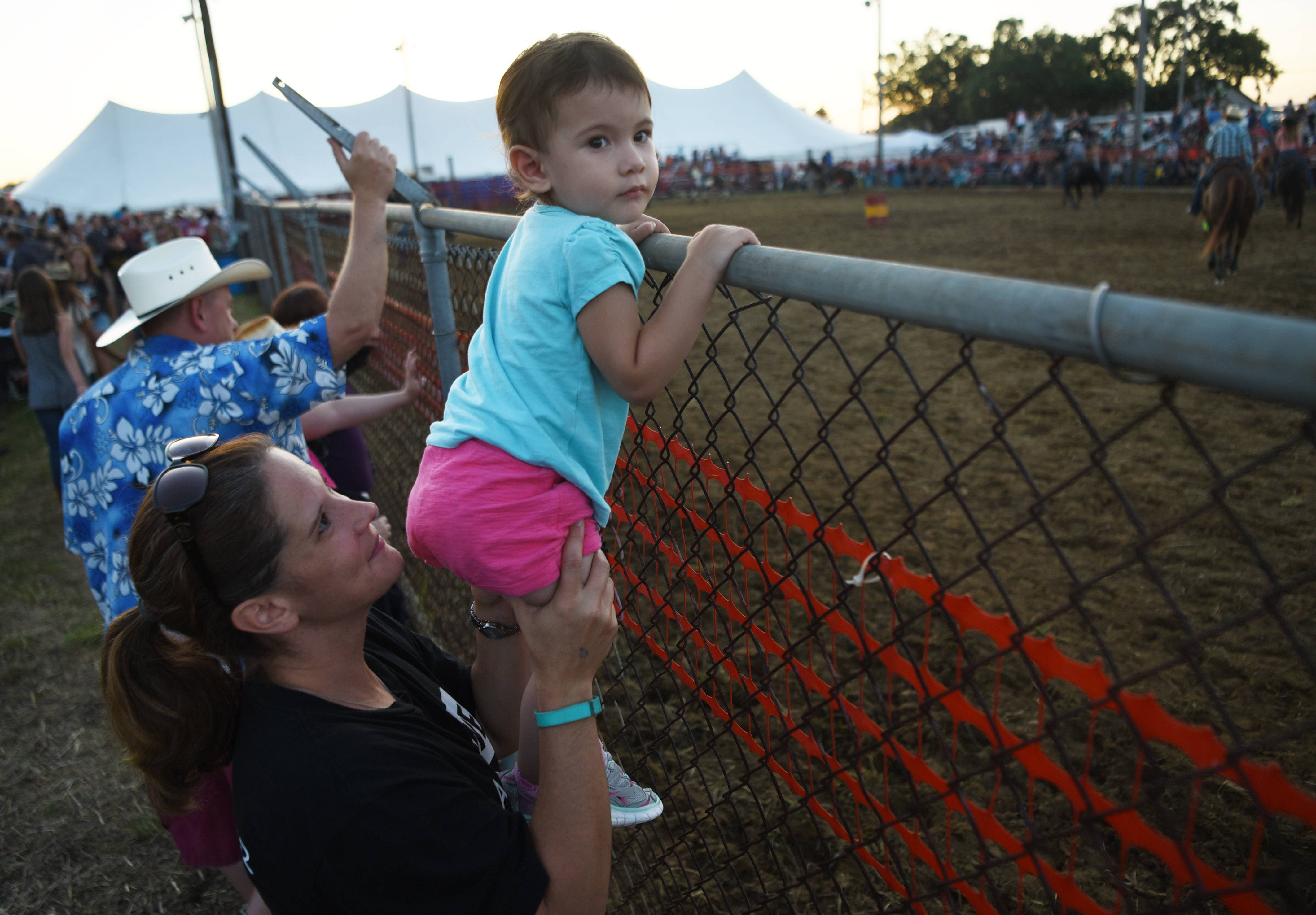Emma Saldana, 2, of Wauconda gets a good look at the horses while getting a boost from her mom, Katie, during intermission at the 54th annual IPRA Championship rodeo Saturday in Wauconda.