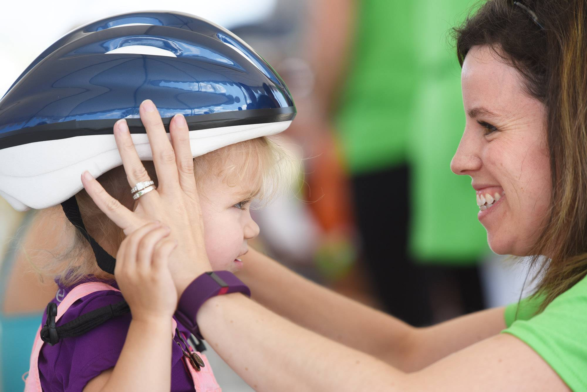 Livianna Hess, 2, has her first bicycle helmet fitted by Meghan Jaske, of Centra Health System at the Centegra Family Health Fest in Huntley Saturday. She was one of 400 children to get a free helmet. Livianna was with her family from Marengo.
