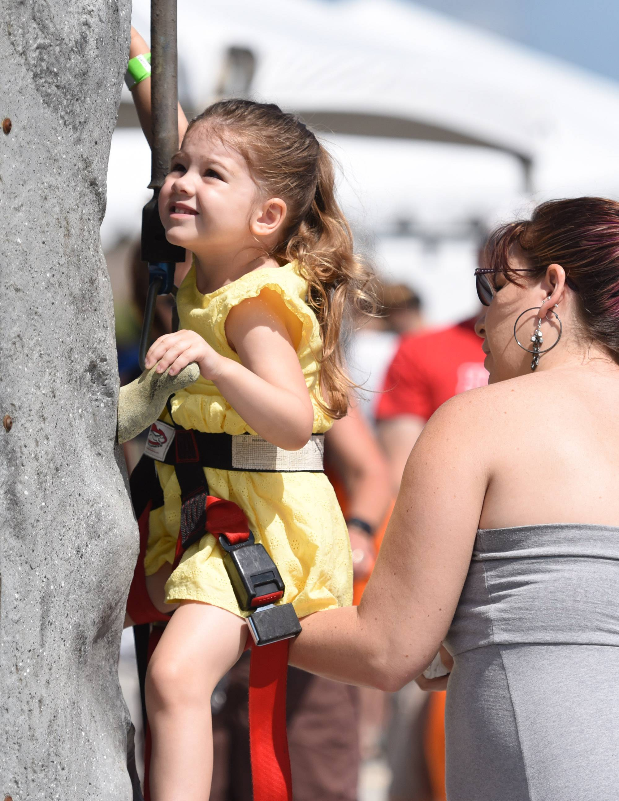 Amber Drago, who turns 4 next month, climbs a rock wall with a little boost from her mother Heather, of Lake in the Hills at the Centegra Family Health Fest in Huntley Saturday.