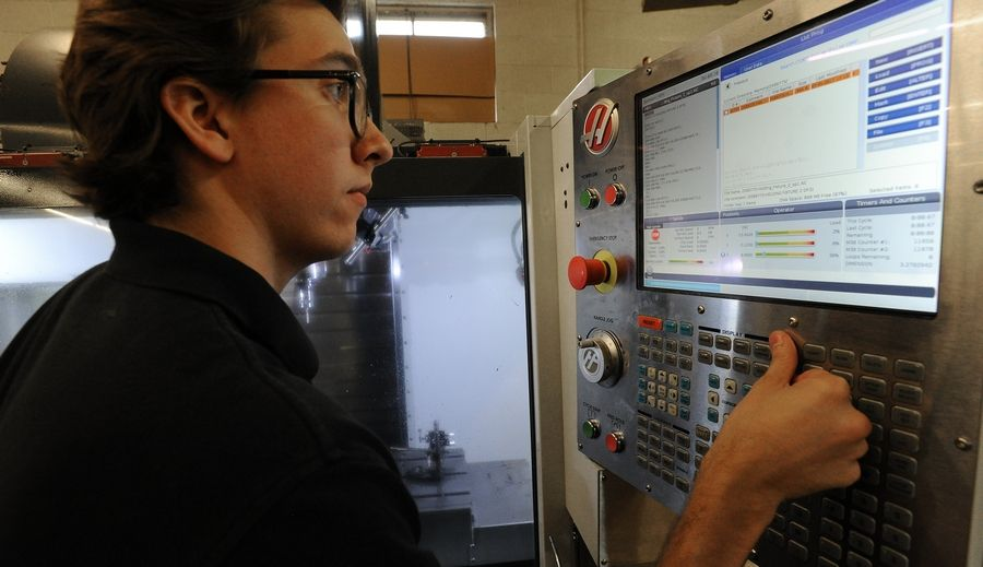 Operations manager Ryan Carr sets up a computer numerical control machine at Carr Machine & Tool Inc. in Elk Grove Village. Carr, like other companies statewide, has a hard time finding skilled workers to fill jobs.