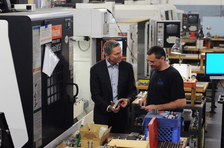Owner Jim Carr works with Serge Shelepov at his Elk Grove Village machine and tool business.