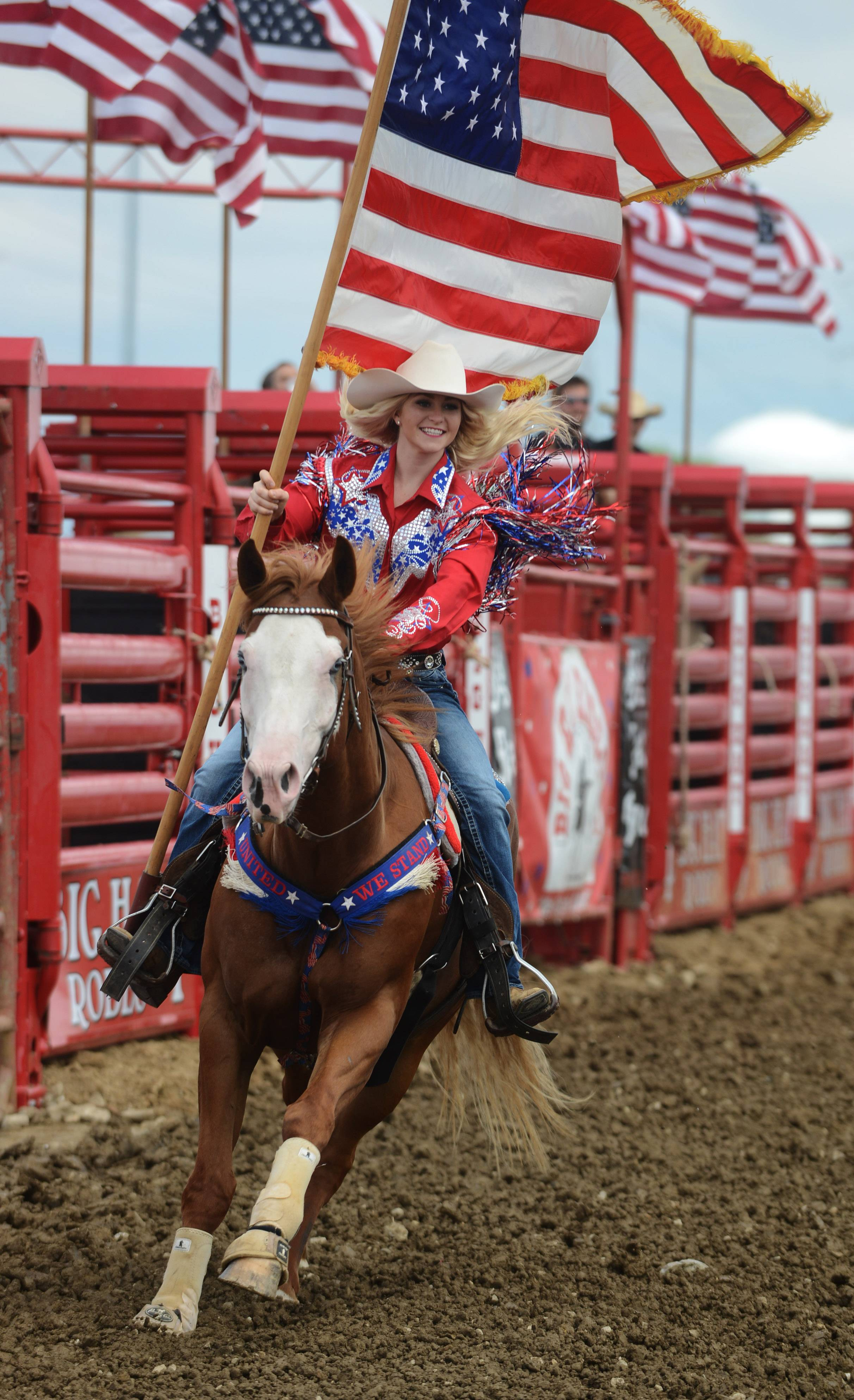 Hannah Ritter of Clinton, Ill., rides with the American flag at the start of the rodeo during last year's Lake County Fair in Grayslake.