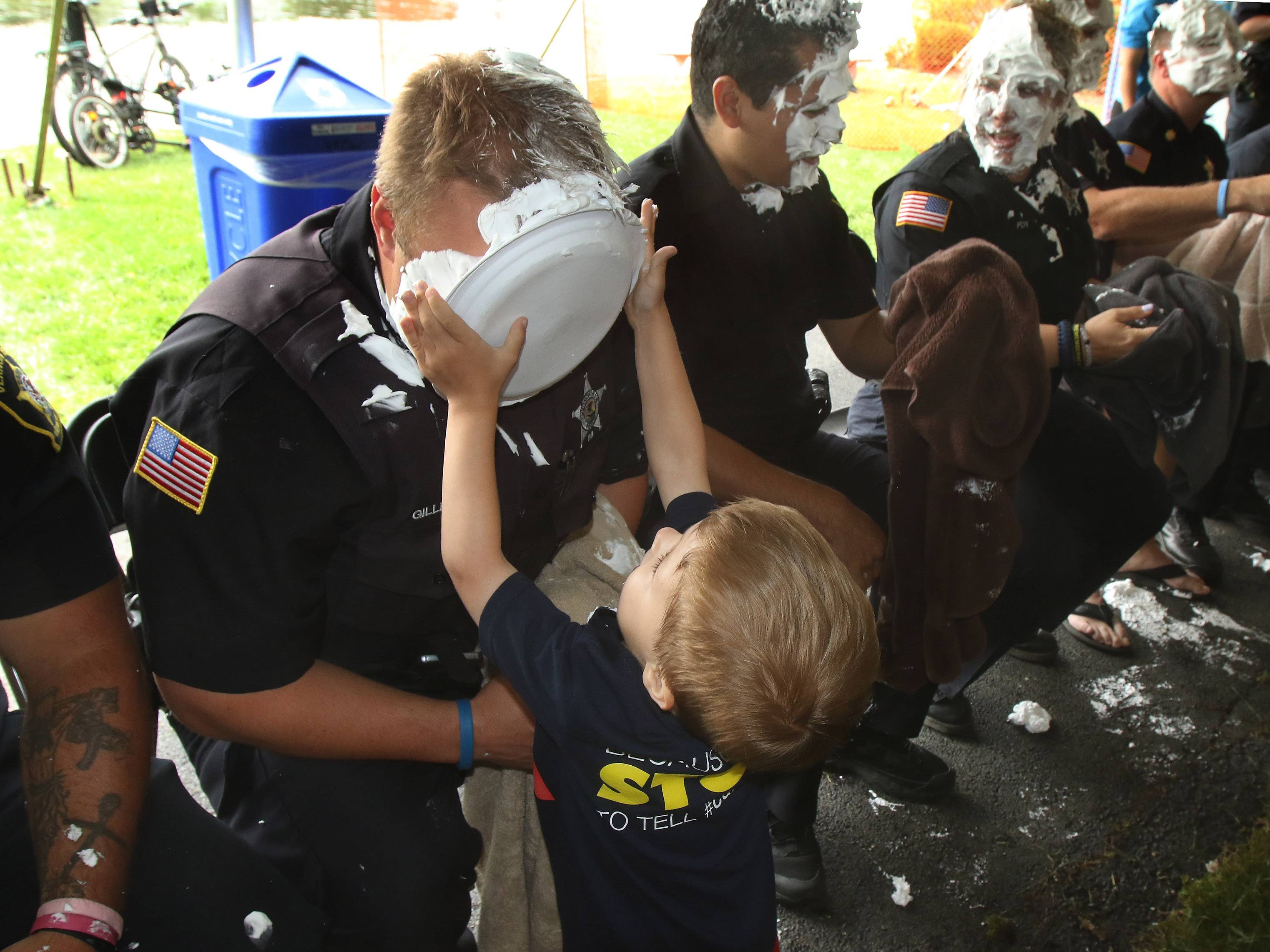 Vernon Hills Det. Andrew Gillespie receives a pie in the face from his son, Joshua, 3, during the last day of the Vernon Hills' Summer Celebration on Sunday at Century Park.