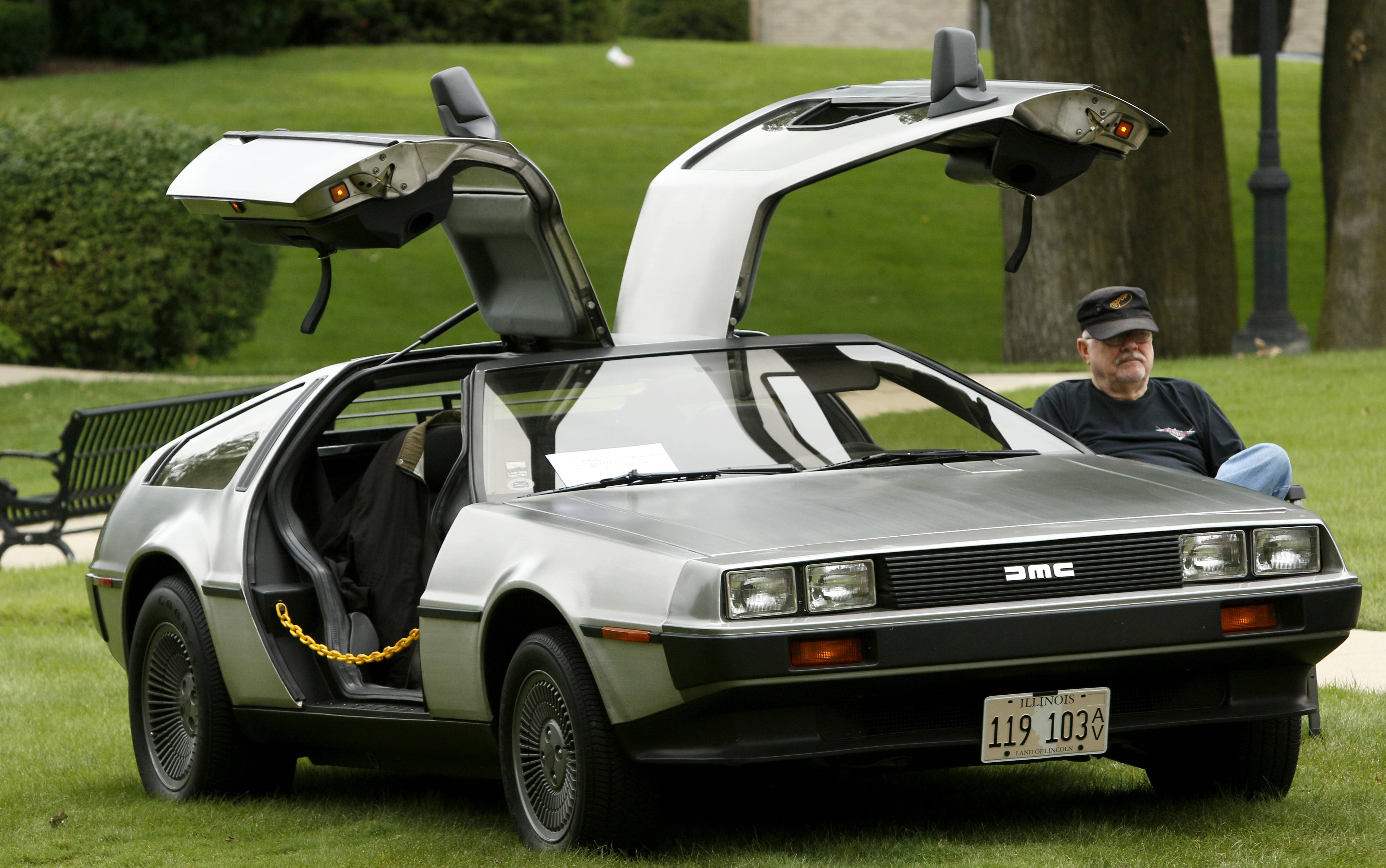 Raph Sandstrom of Elk Grove relaxes Sunday next to his 1981 DeLorean DMC-12 at a car show during the last day of Itasca Fest.