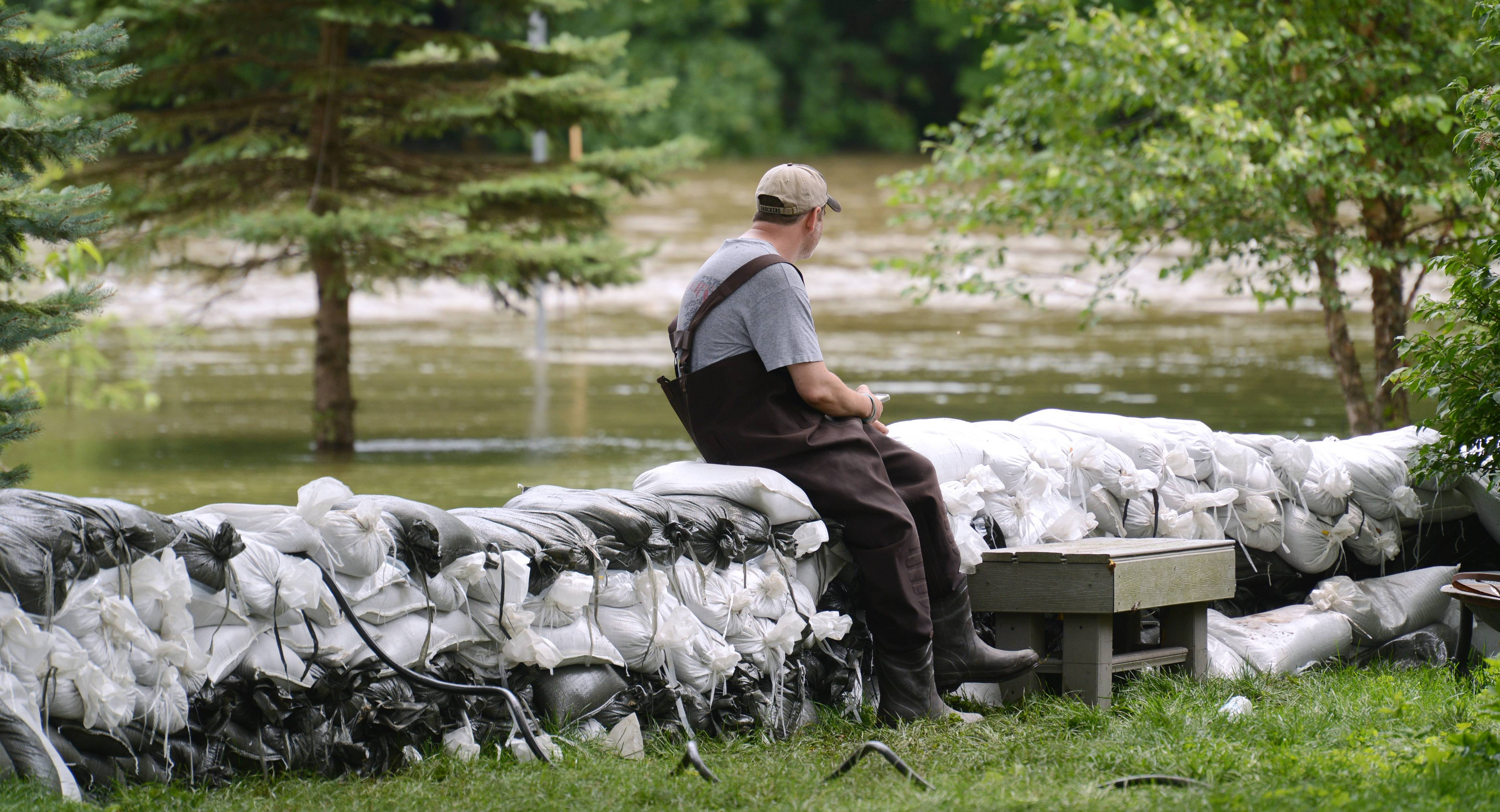 Algonquin resident Dan Prokop keeps an eye on the rising Fox River Sunday at his La Fox River Drive home. Prokop said he and his family began building a wall of sandbags Thursday.