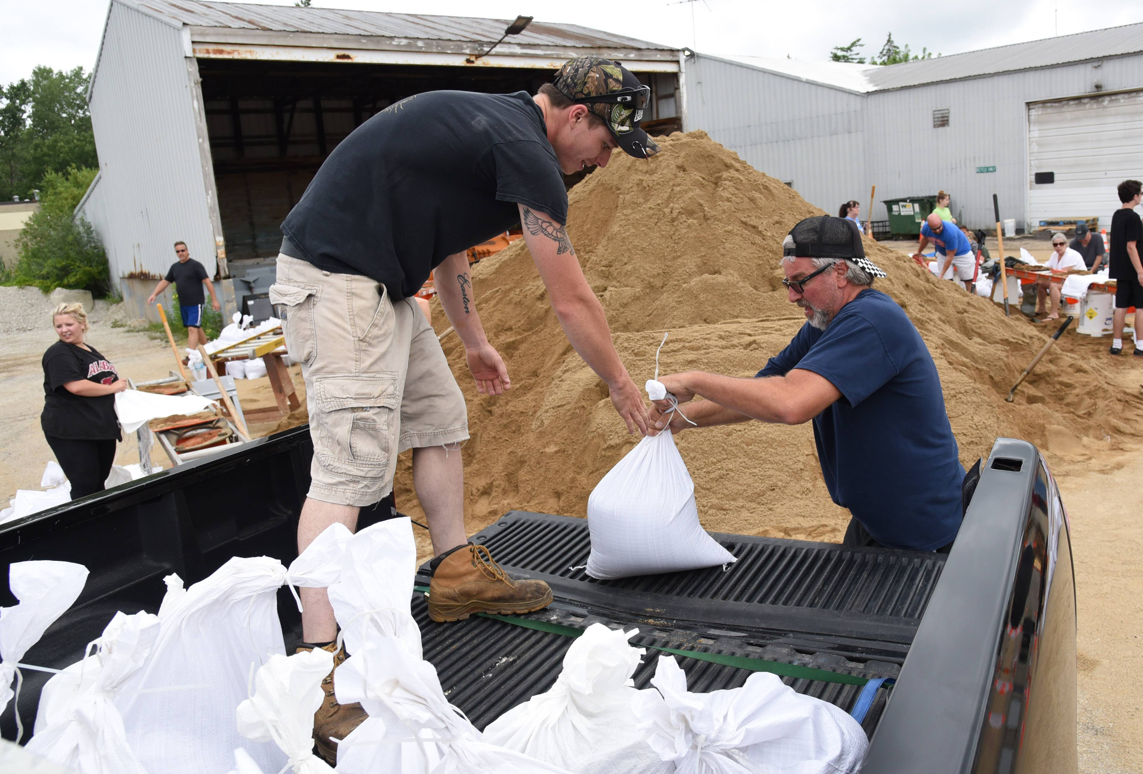 Volunteer Cory Wedge of Round Lake, left, helps Fox Lake resident Dan Vezensky load his truck with sandbags Sunday morning at the Fox Lake Public Works facility.