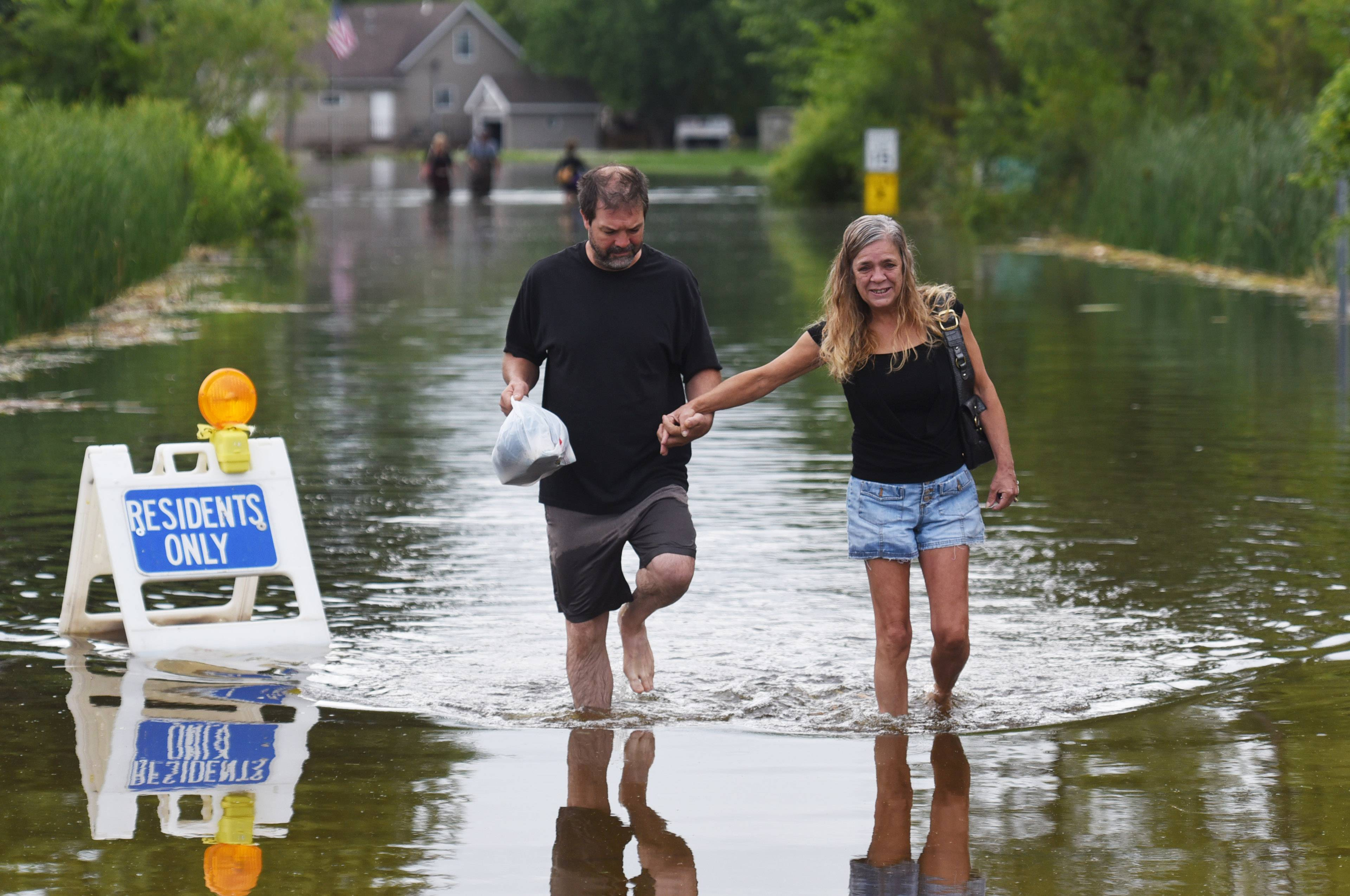 Dan Robinson and April Cissell walk through the flooded Knollwood Road in Ingleside Sunday morning. Knollwood Park subdivision residents have been parking along Route 59 and taking a boat or wading through the water to get to their homes.