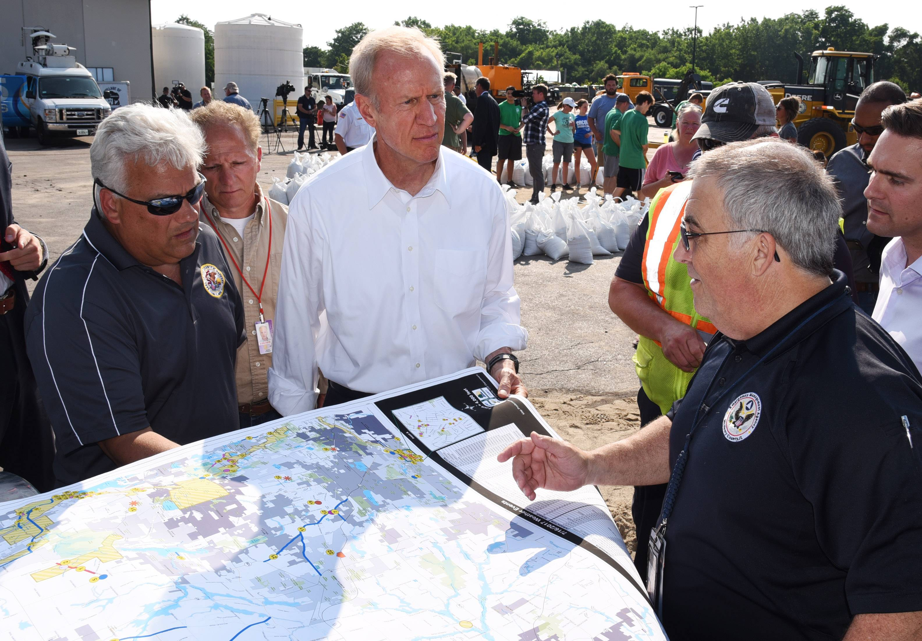 Gov. Bruce Rauner, center, looks at a flood inundation and road closure map with McHenry County Emergency Management Director David Christensen, right, and McHenry County Board Chairman Jack Franks, left, on Sunday at Algonquin's public works facility.