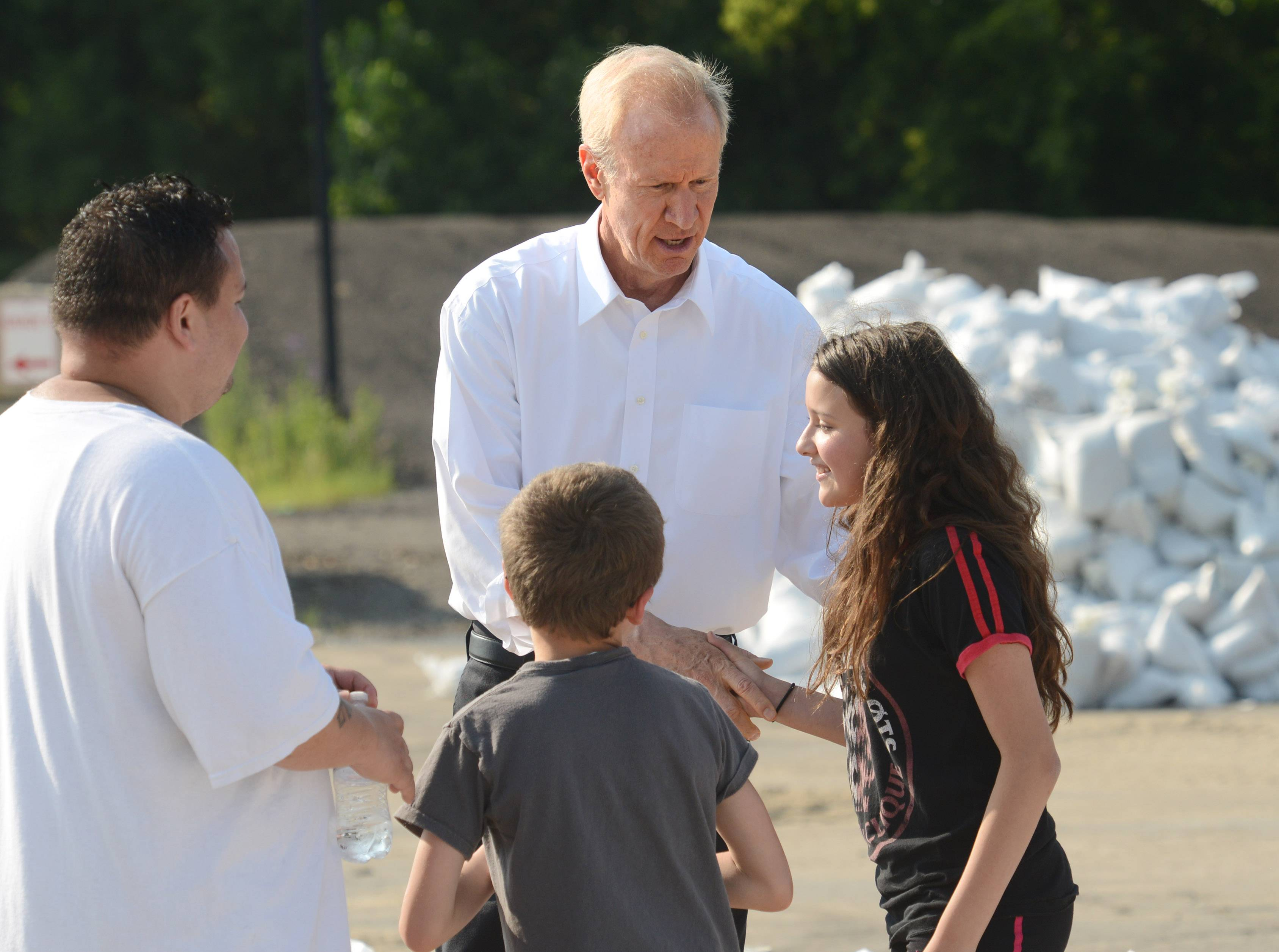 South Elgin resident Manuel Ramirez, left, brought his children Caleb, 11, and Cadence, 12 right, to volunteer filling sandbags Sunday at the Algonquin public works facility. While working, they were thanked by Gov. Bruce Rauner.