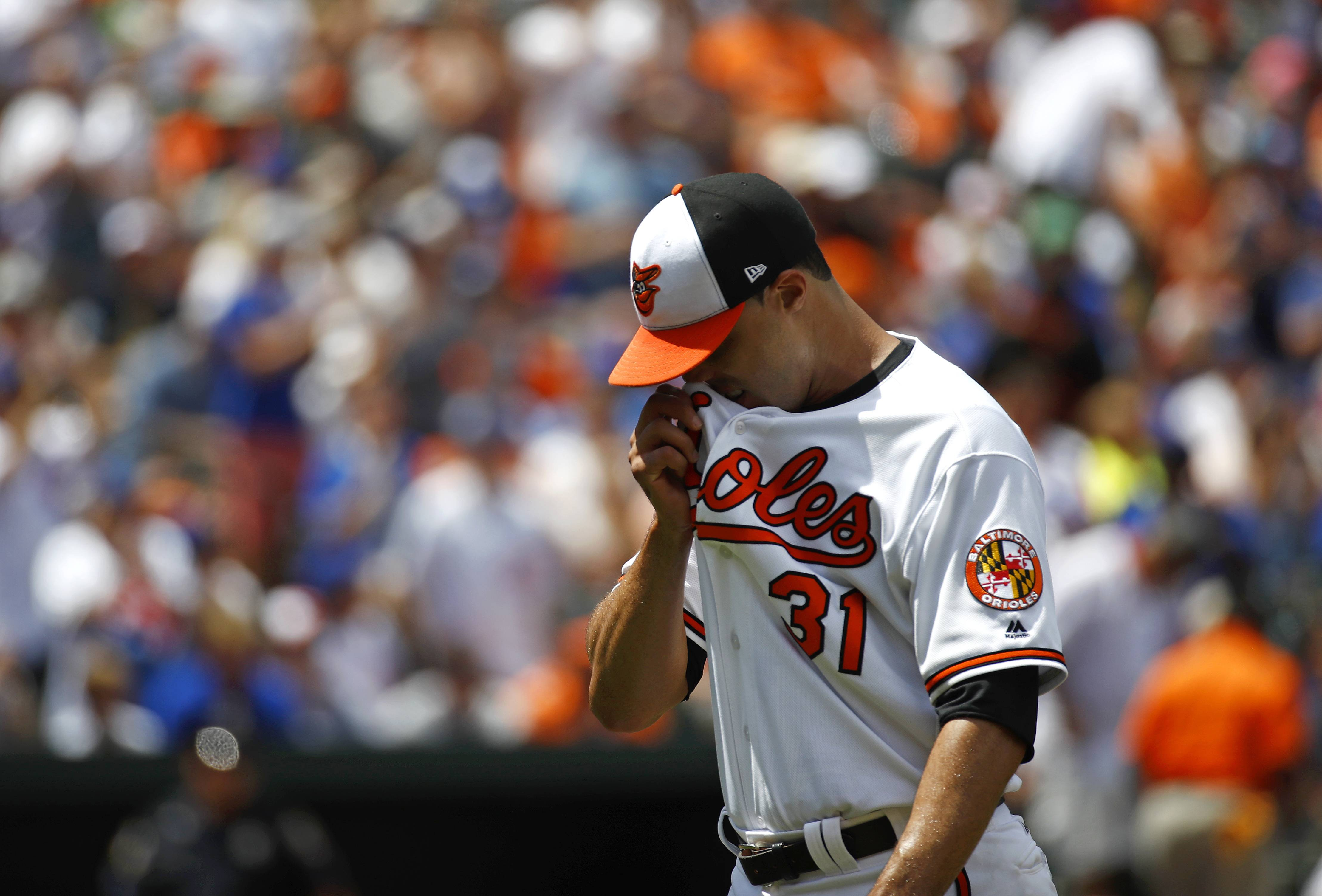 Baltimore Orioles starting pitcher Ubaldo Jimenez wipes his face as he walks off the field after the top of the second inning of a baseball game against the Chicago Cubs in Baltimore, Sunday, July 16, 2017. Chicago scored four runs against Jimenez in the second.