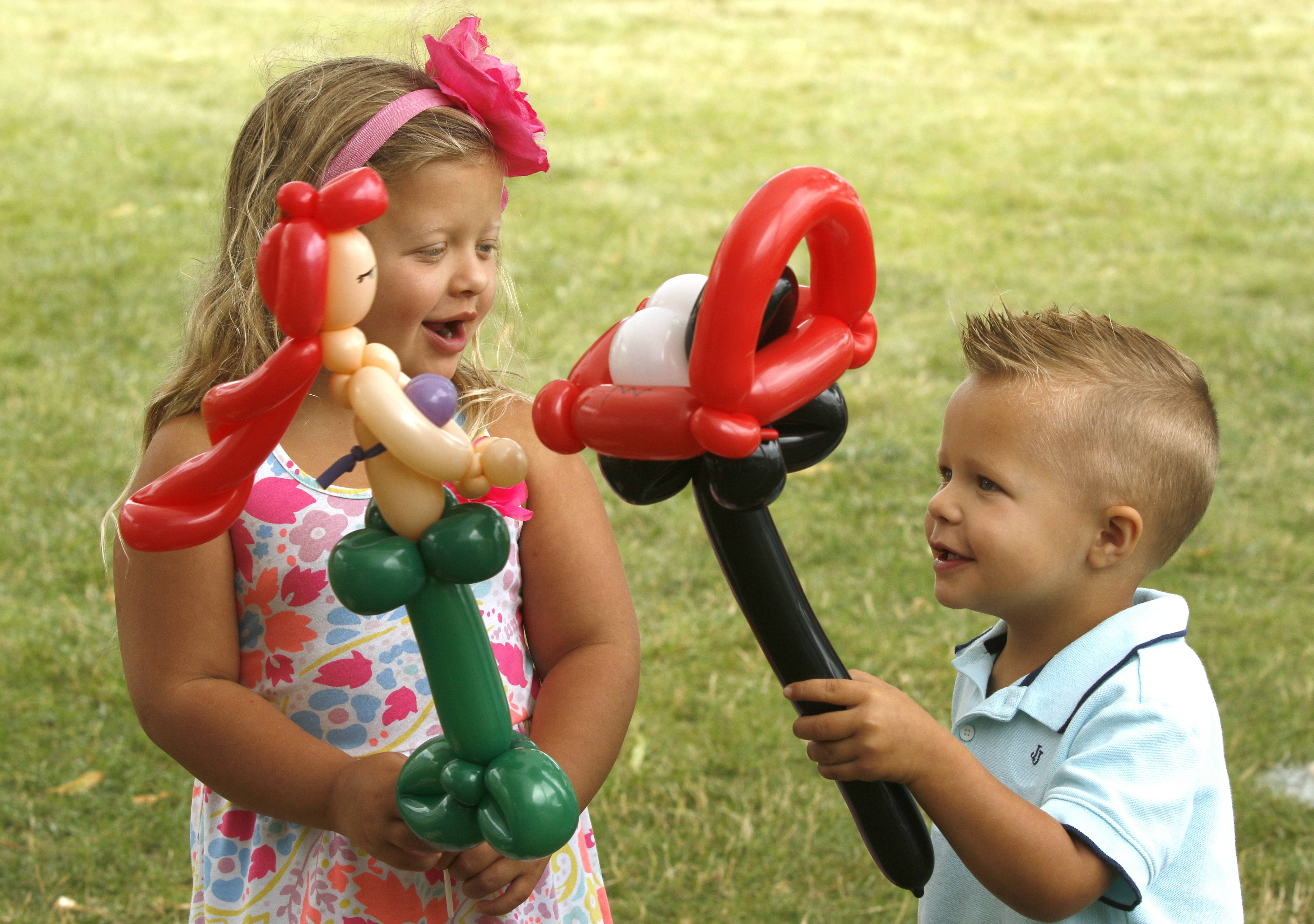 Kimber Gruber, 5, left, and her brother Landon, 3, right, of Itasca show each other balloons made by Custers Family Entertainment on Sunday, while enjoying the final hours of Itasca Fest.