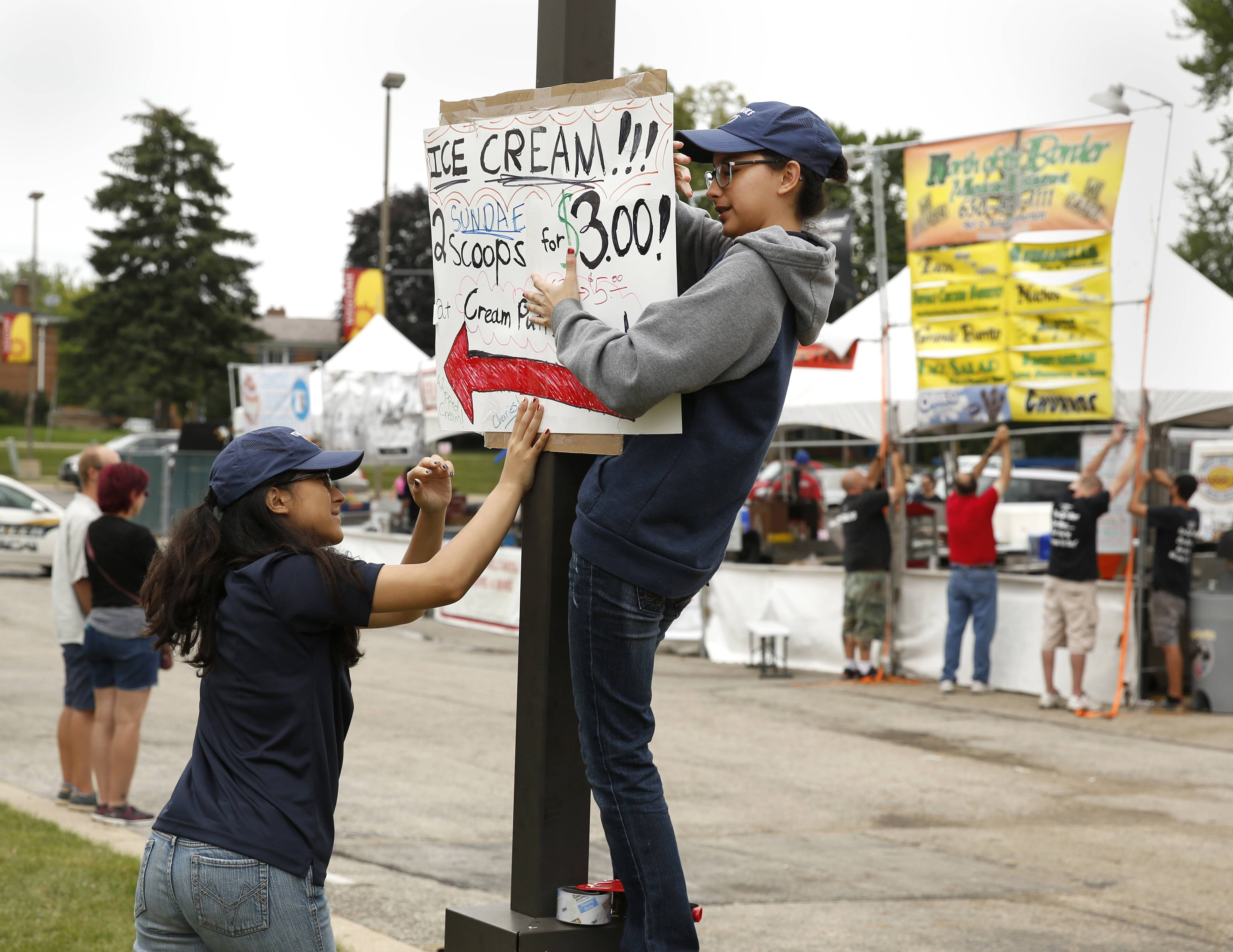 Hannah Avila, left, and her sister Aya Avila, right, put up a sign to direct customers to their ice cream and crème puffs stand Sunday during the last day of Itasca Fest.
