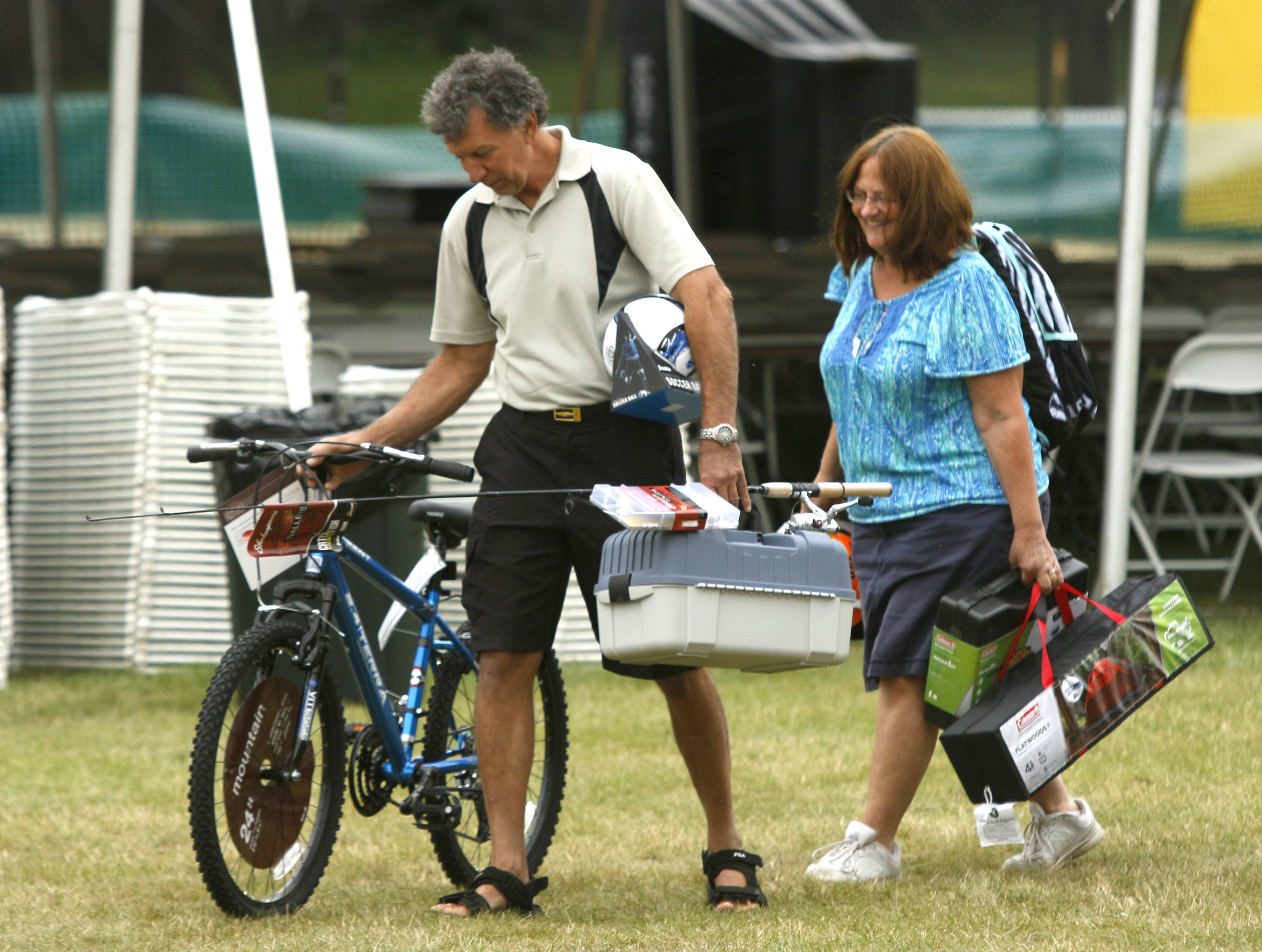 Mike Heppner and his wife Nancy won several prizes Sunday, including the fishing contest award raffled by the Lions Club, during the last day of Itasca Fest.