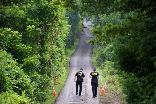 Pennsylvania State Police officers walk up a driveway, Friday, July 14, 2017, in Solebury, Pa., as the investigation of four missing young Pennsylvania men continues. Lawyer Paul Lang, a defense attorney for Cosmo DiNardo, said Thursday that his client has admitted killing the four men who went missing last week and told authorities the location of the bodies. Lang says prosecutors agreed to take the death penalty off the table in return for DiNardo's cooperation.
