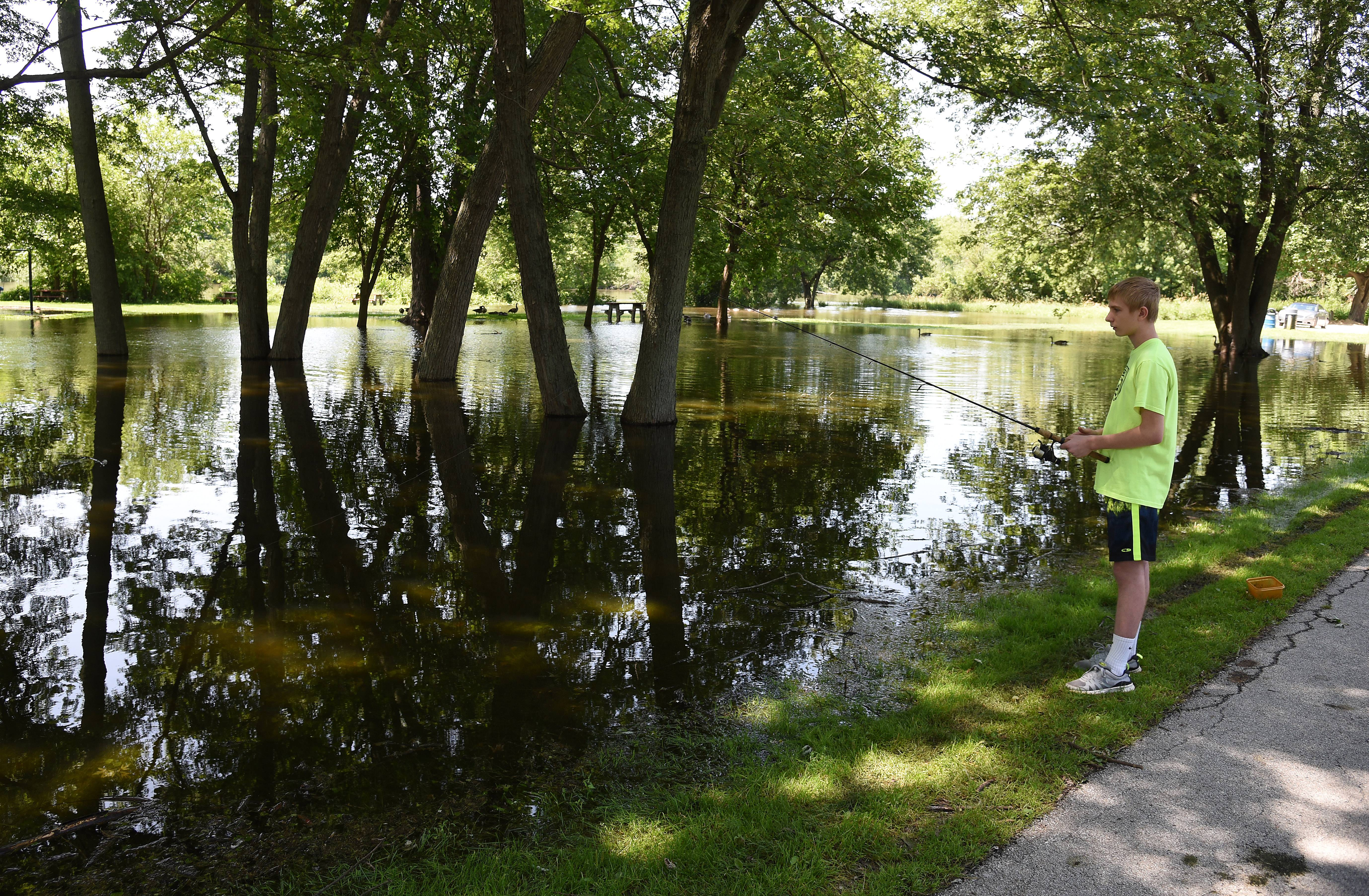 Austin Settipani, 13, takes advantage of flooding at Taly Park in St. Charles to do some fishing about 100 yards away from the usual Fox River bank.