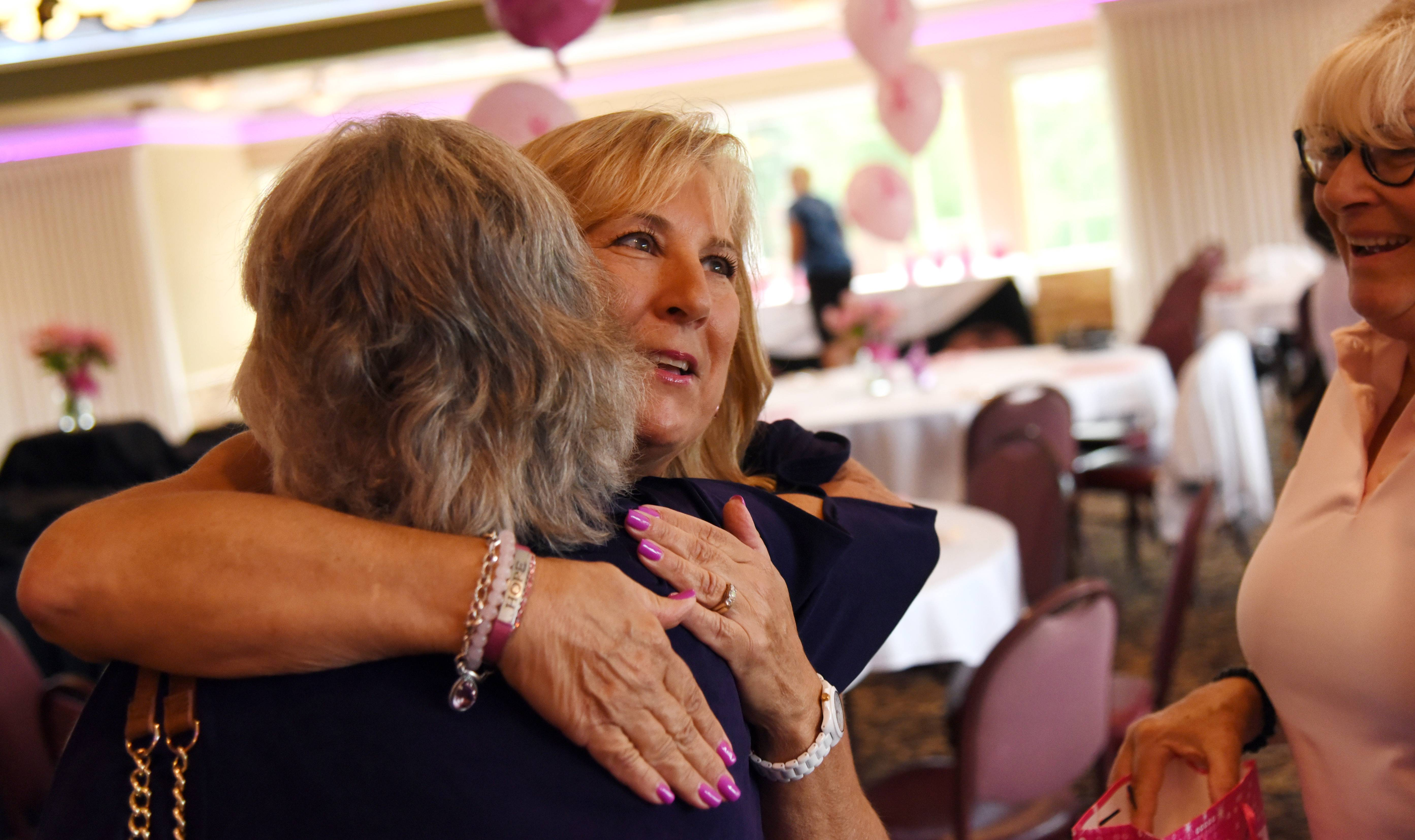 Event organizer Linda Ewing, facing, hugs Cheri Schillo at a golf outing benefiting breast cancer research at Schaumburg Golf Club Monday. Both women are from Schaumburg.
