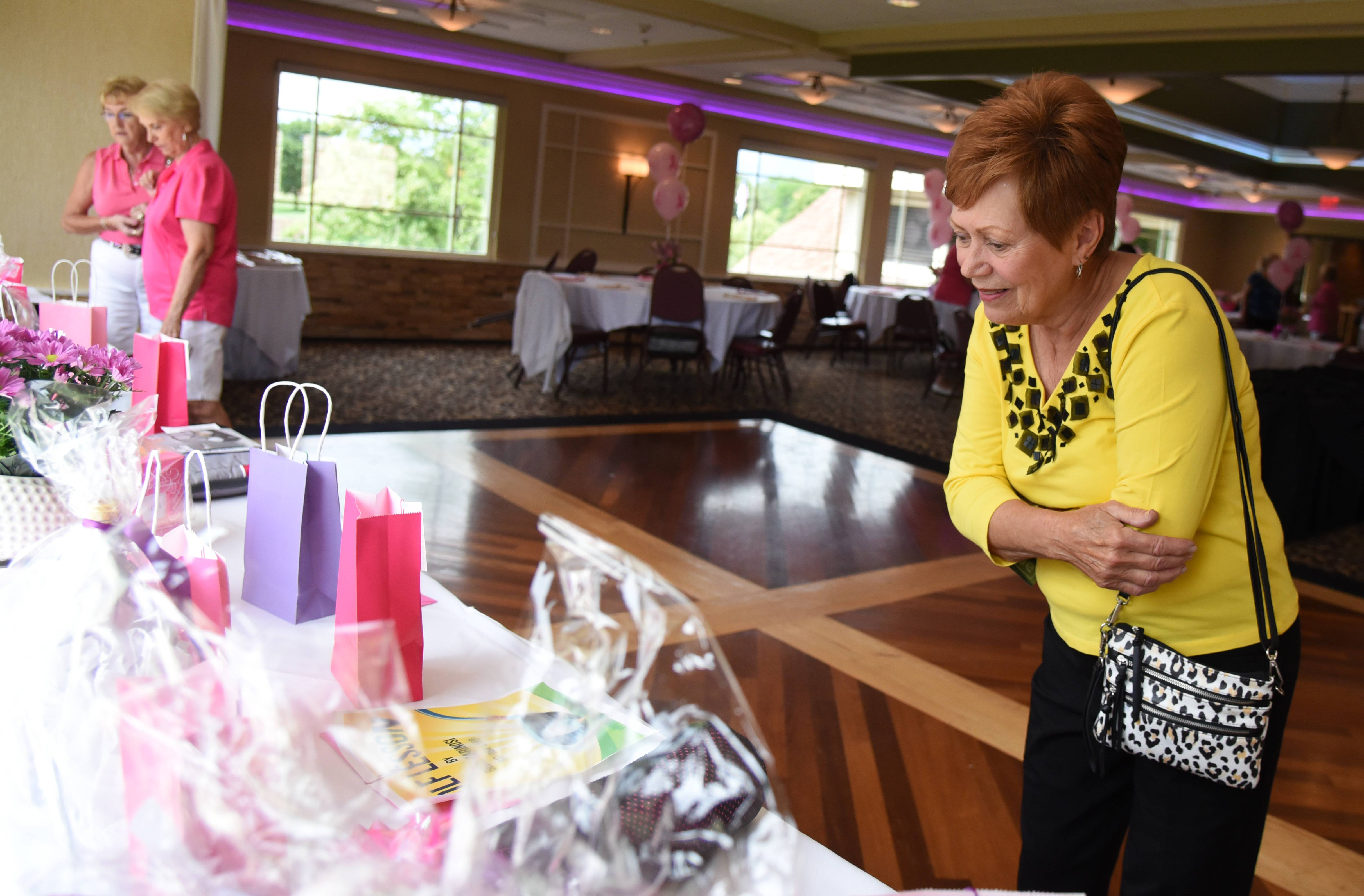 Vicki Casale of Bloomingdale checks out some of the raffle prizes at a golf outing benefiting breast cancer research at Schaumburg Golf Club Monday.