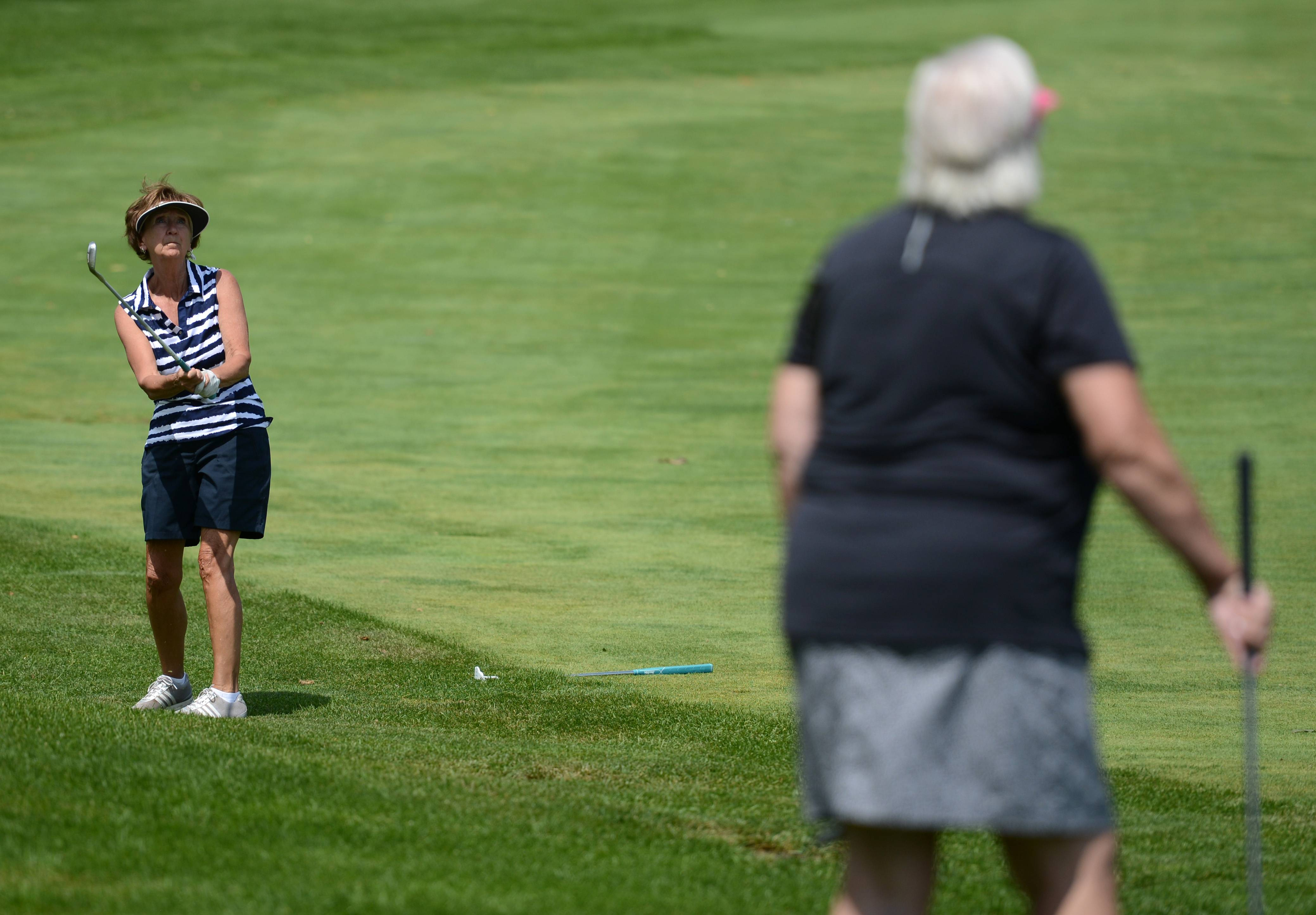 Margie Krizizke of Schaumburg, along with playing partner Judy Wanish, watch her chip as it heads toward the green during a golf outing benefiting breast cancer research at Schaumburg Golf Club Monday. Wanish is from Mishicot, Wisconsin.