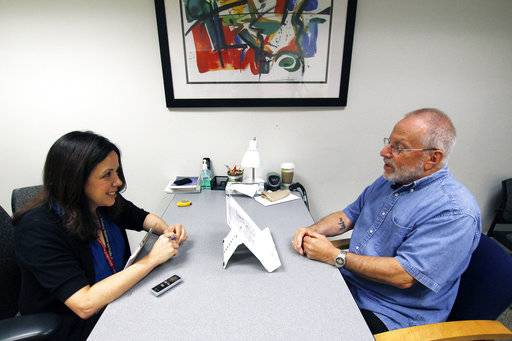 In this July 6, 2017 photo, Kim Mueller, left, administers a test to Alan Sweet, in which he describes an illustration, as part of a University of Wisconsin-Madison study on dementia. The study found that for some people subtle changes in everyday speech can be correlated with early mild cognitive impairment, which can be a precursor to Alzheimer's disease. (AP Photo/Carrie Antlfinger)