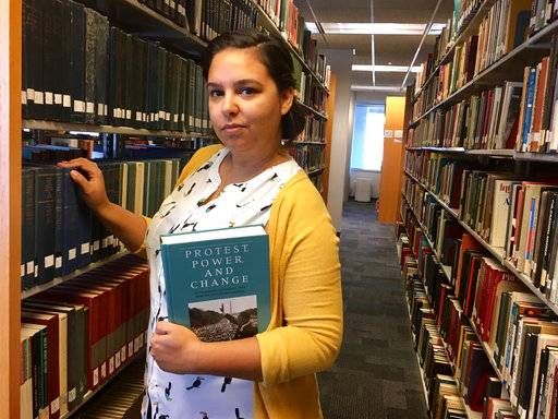 "This Tuesday, July 11, 2017 photo shows Alexandra Flores in the Nelson Poynter Memorial Library on the University of South Florida St. Petersburg campus. Flores, 29, works as a library assistant while pursuing a master's degree in library science. She credits the Obama health law for her decision to go back to school rather than be locked into her previous office job. ""Without health care, I wouldn't feel comfortable growing my career the way I have,"" Flores said. (Natalie Polson via AP)"