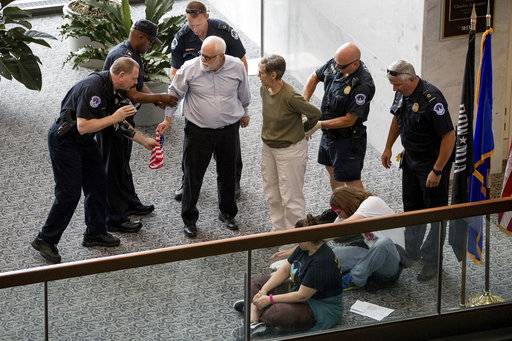 Capitol Hill police officers arrest a group protesting the Republican healthcare bill outside the offices of Sen. Dean Heller, R-Nev., on Capitol Hill in Washington, Monday, July 17, 2017. The Senate has been forced to put the republican's health care bill on hold for as much as two weeks until Sen. John McCain, R-Ariz., can return from surgery. (AP Photo/Andrew Harnik)
