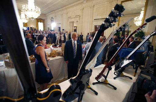 "President Donald Trump, second from left, looks at Gibson Guitars, made in Tennessee, during a ""Made in America,"" product showcase featuring items created in each of the U.S. 50 states, at the White House, Monday, July 17, 2017, in Washington. (AP Photo/Alex Brandon)"